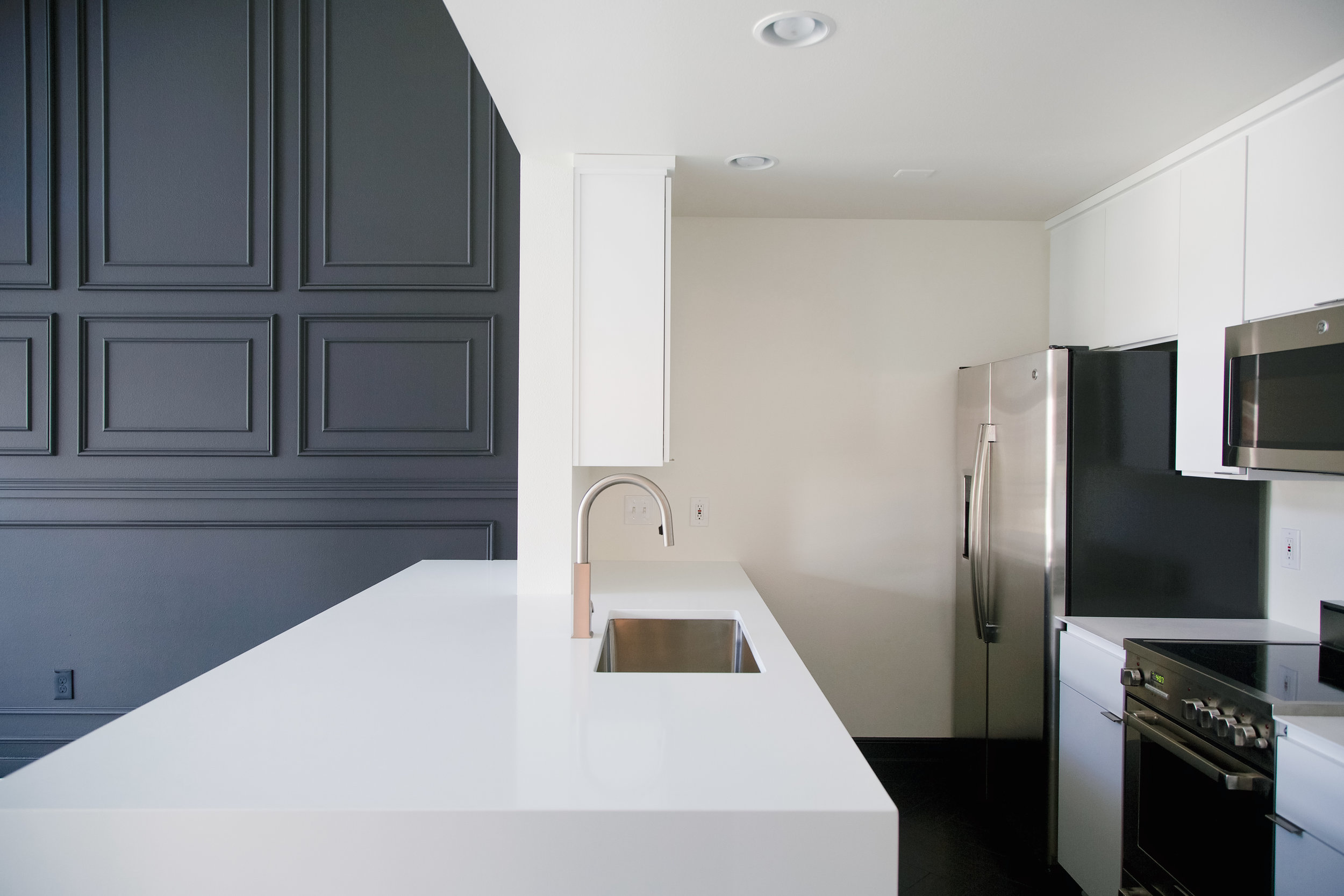 Modern kitchen with clean white pental quartz countertops and a Moen faucet.