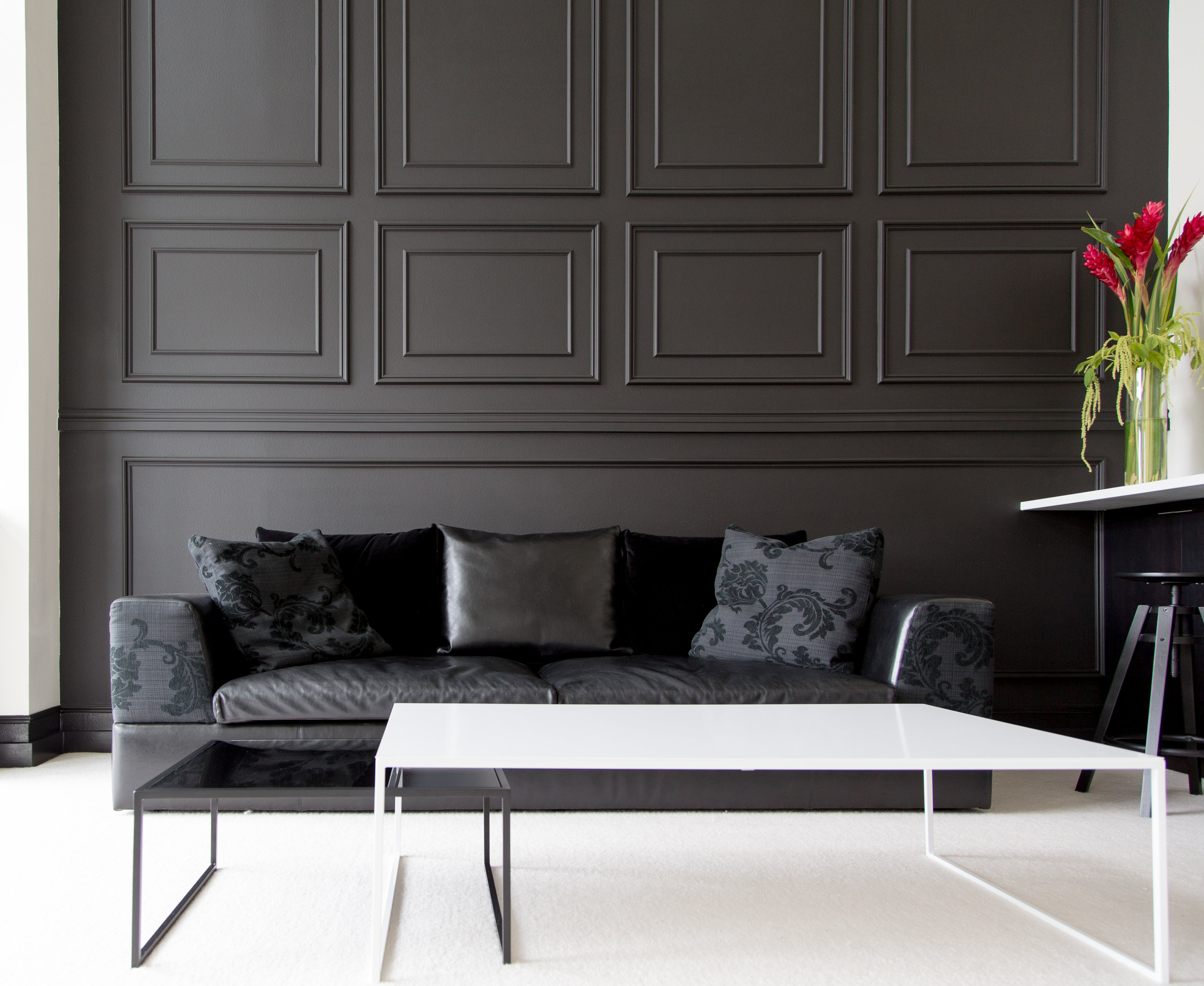 Black millwork and wainscotting in Seattle high-rise condominium with modern coffee table and sofa.