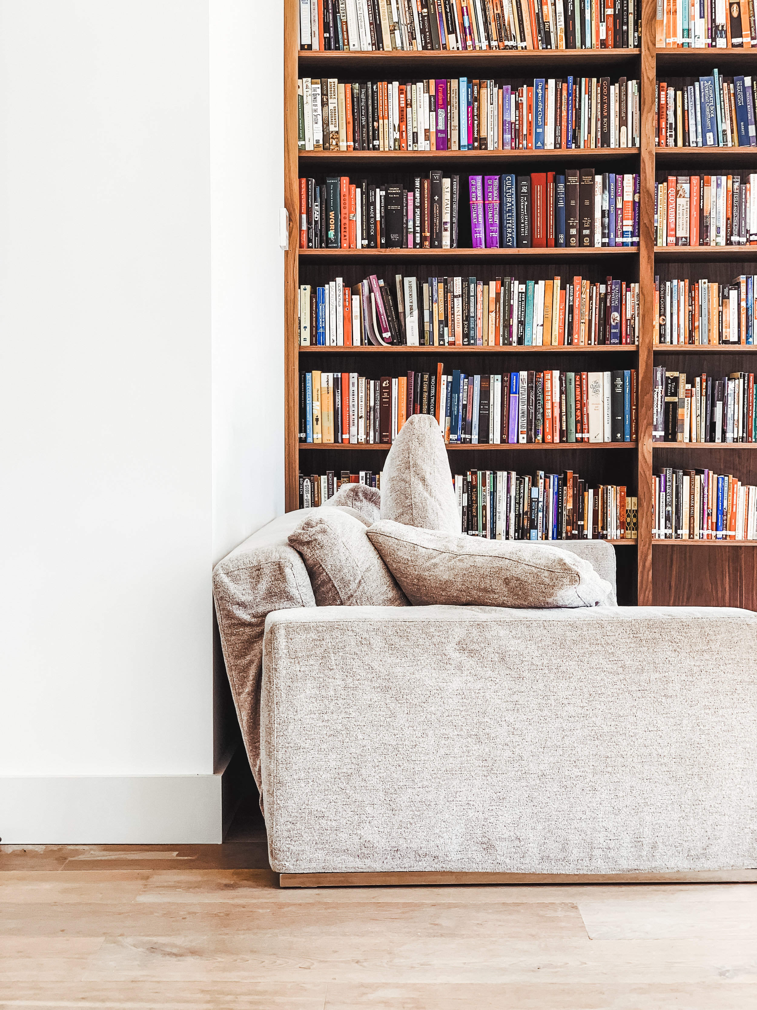 Grey sofa with walnut bookcases and books.