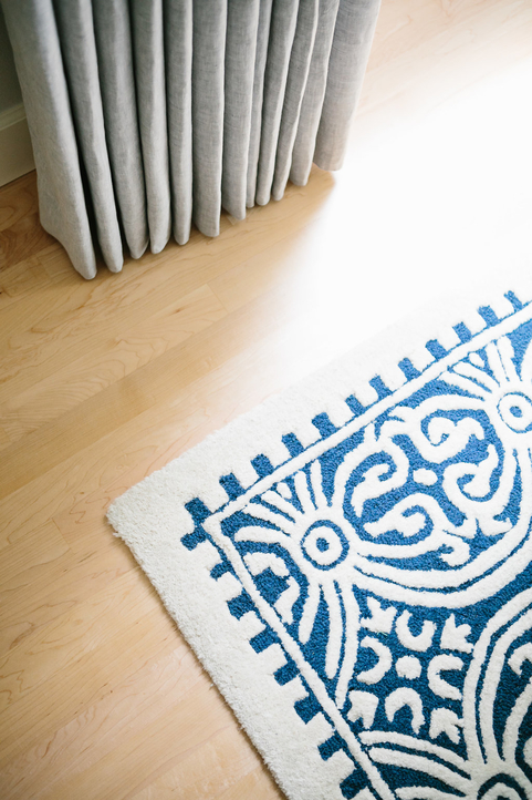 Light hardwood floors with a heavy patterned rug and custom drapery.
