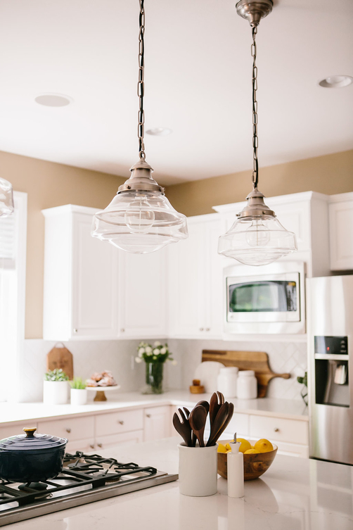 A bright white kitchen with white countertops and cabinets, stainless steel appliances, glass pendants and interior decorations on the island.