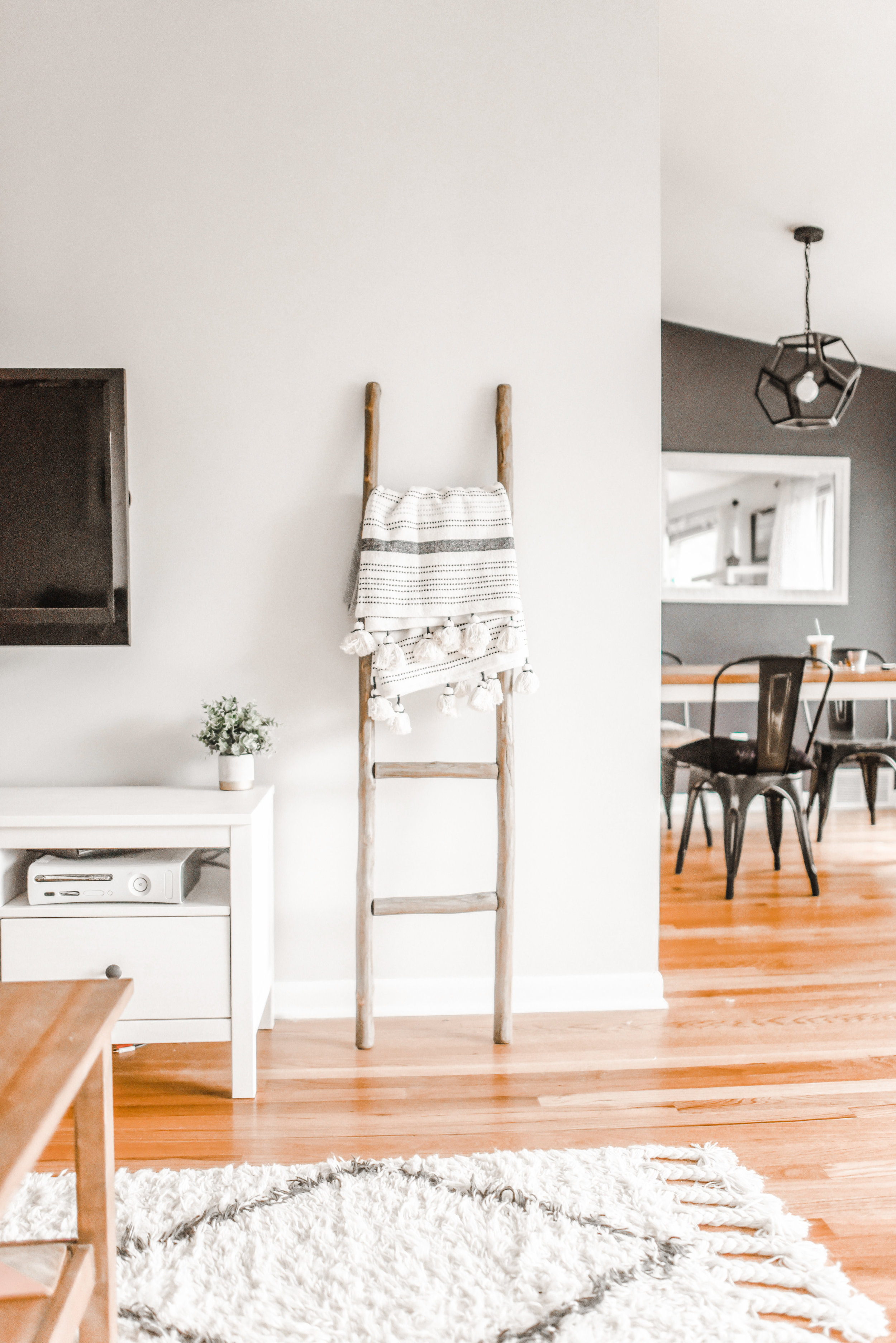 Hardwood floors and white walls flood this home with natural light designed by Elegant Simplicity Interiors.