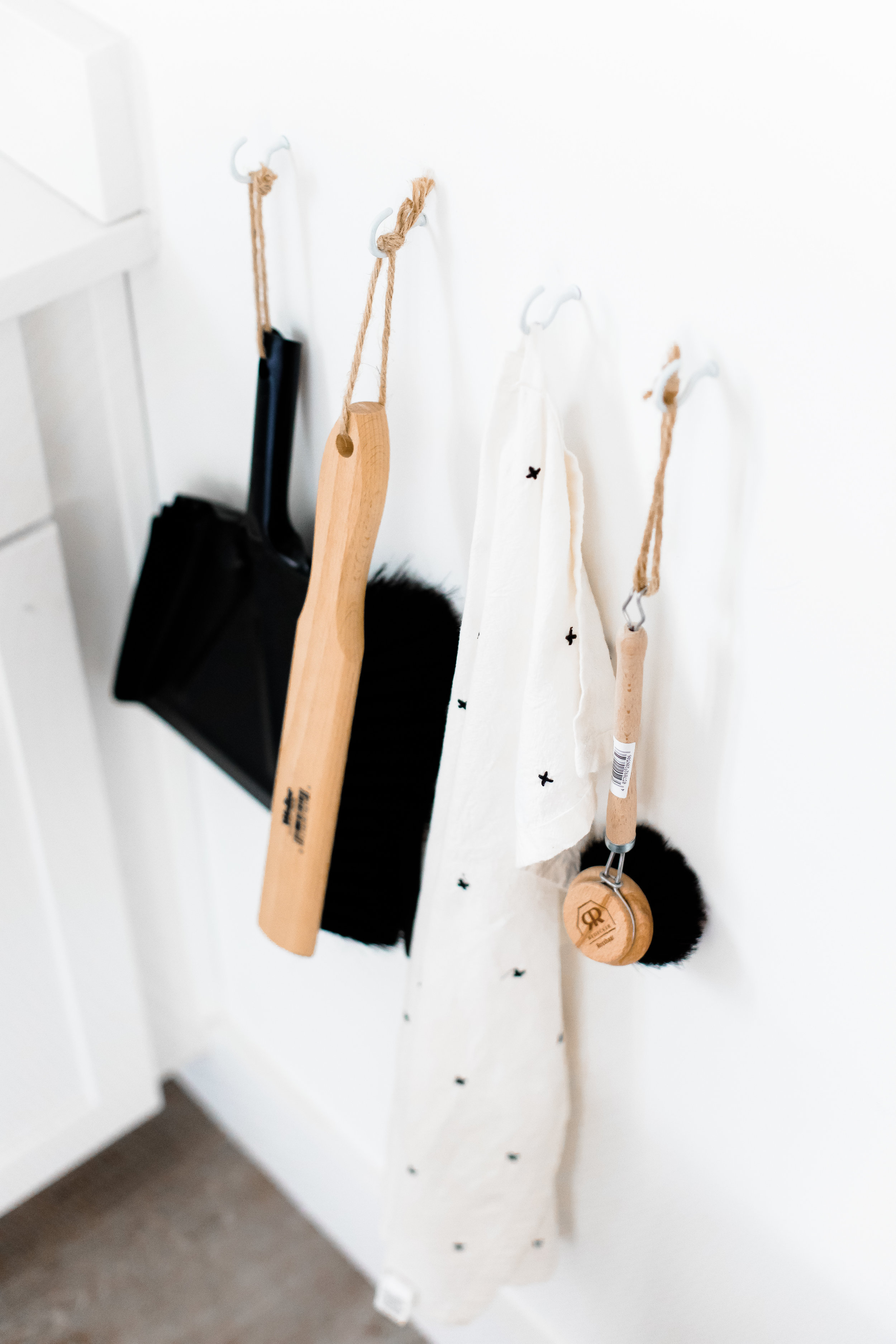 An organized pantry closet with a rag, broom and dust pan.