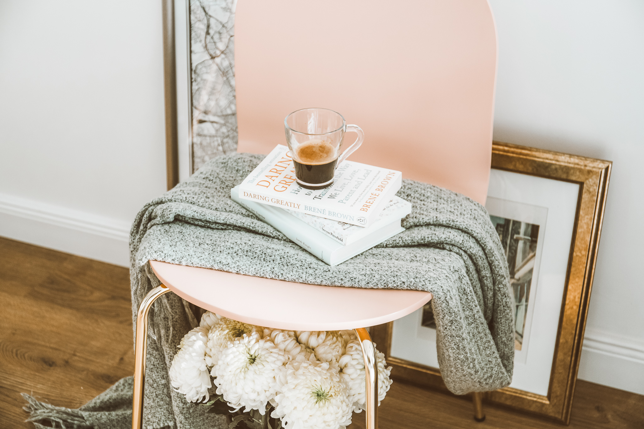 Coffee, books, blankets, flowers tossed on a chair in living room.