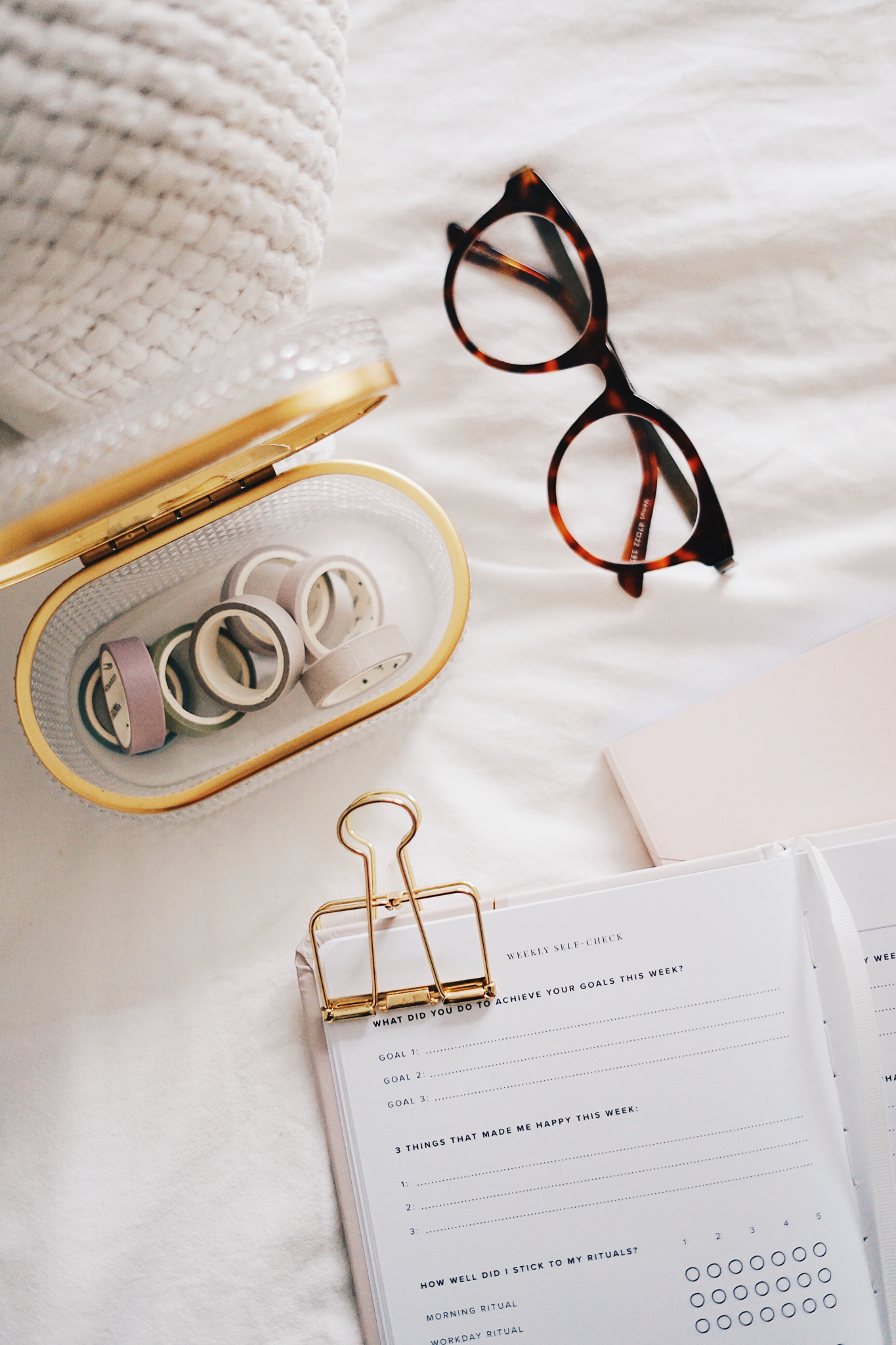 Glasses, tape and an old fashioned paper organizer laid on the bed.