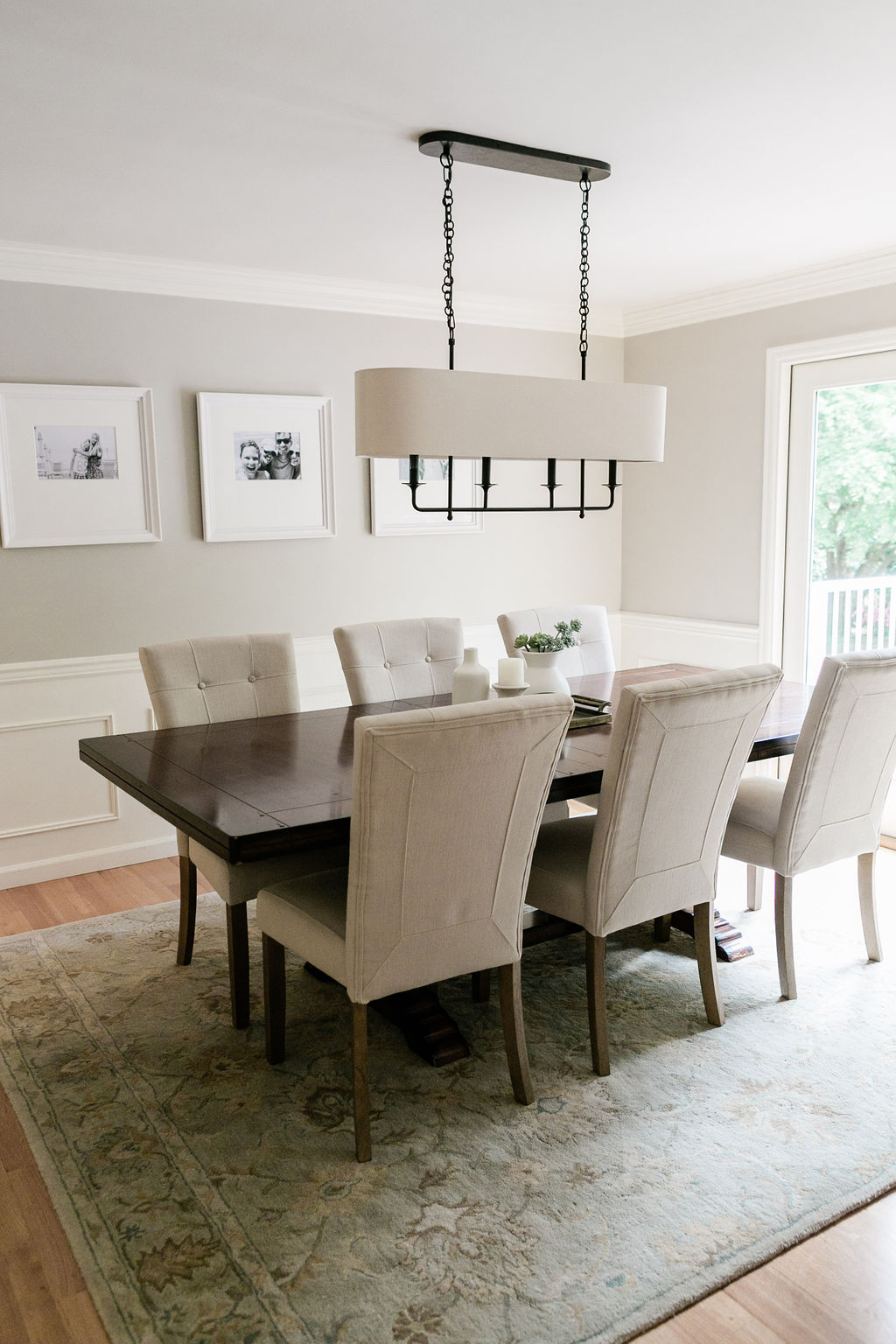 Solid wood dining table with upholstered parson style chairs and white wainscoting.