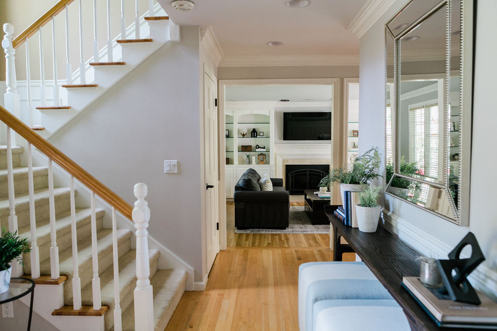 Entryway of a home with switchback stairs and hardwood floors.