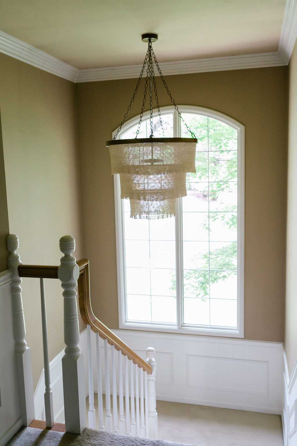 Stairwell Chandelier, with wood banister and white millwork.