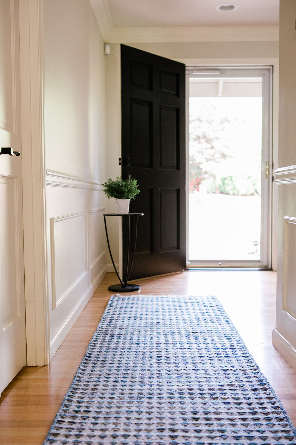 Navy blue entryway runner with black door and white millwork.