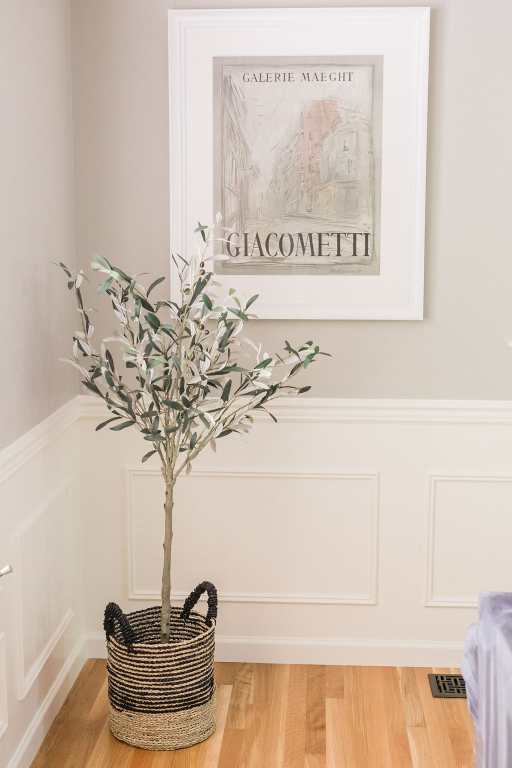 Faux tree in a basket with custom artwork, white millwork and hardwood floors.