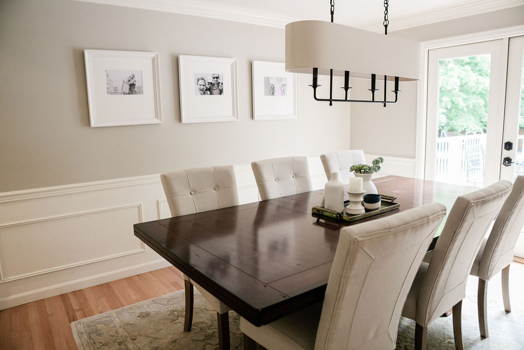 Dining table with bronze tray and large area rug.