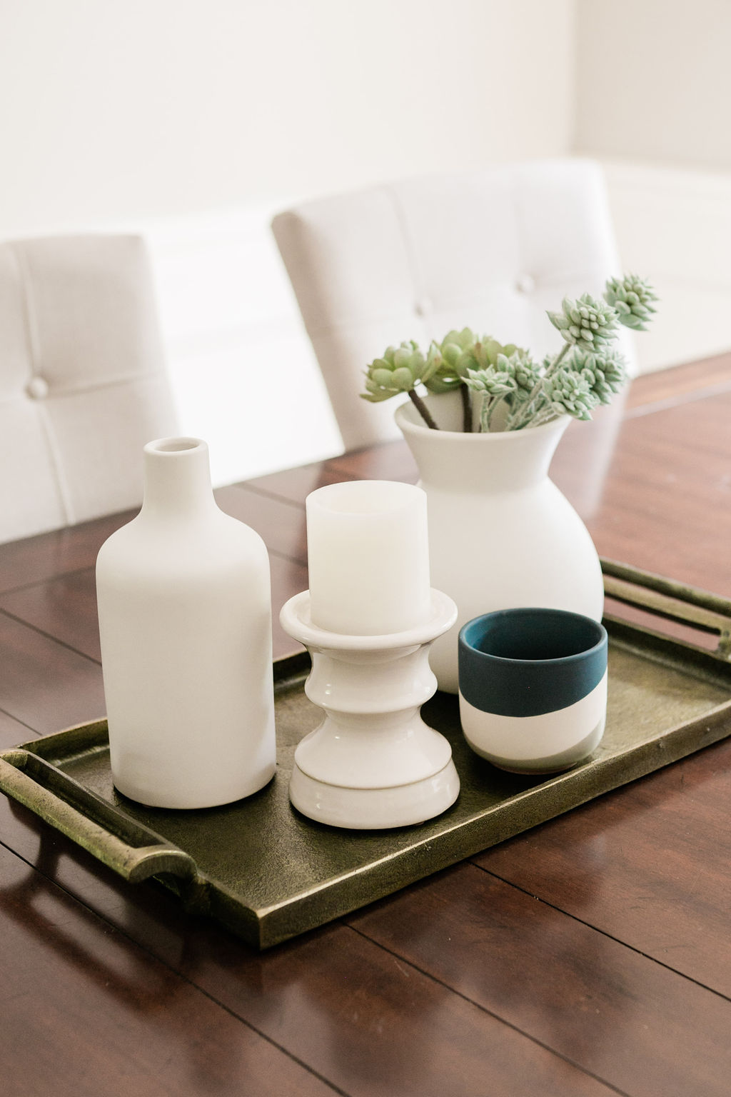 Accessories, vases and a bronze tray on a solid wood table styled by an interior decorator.