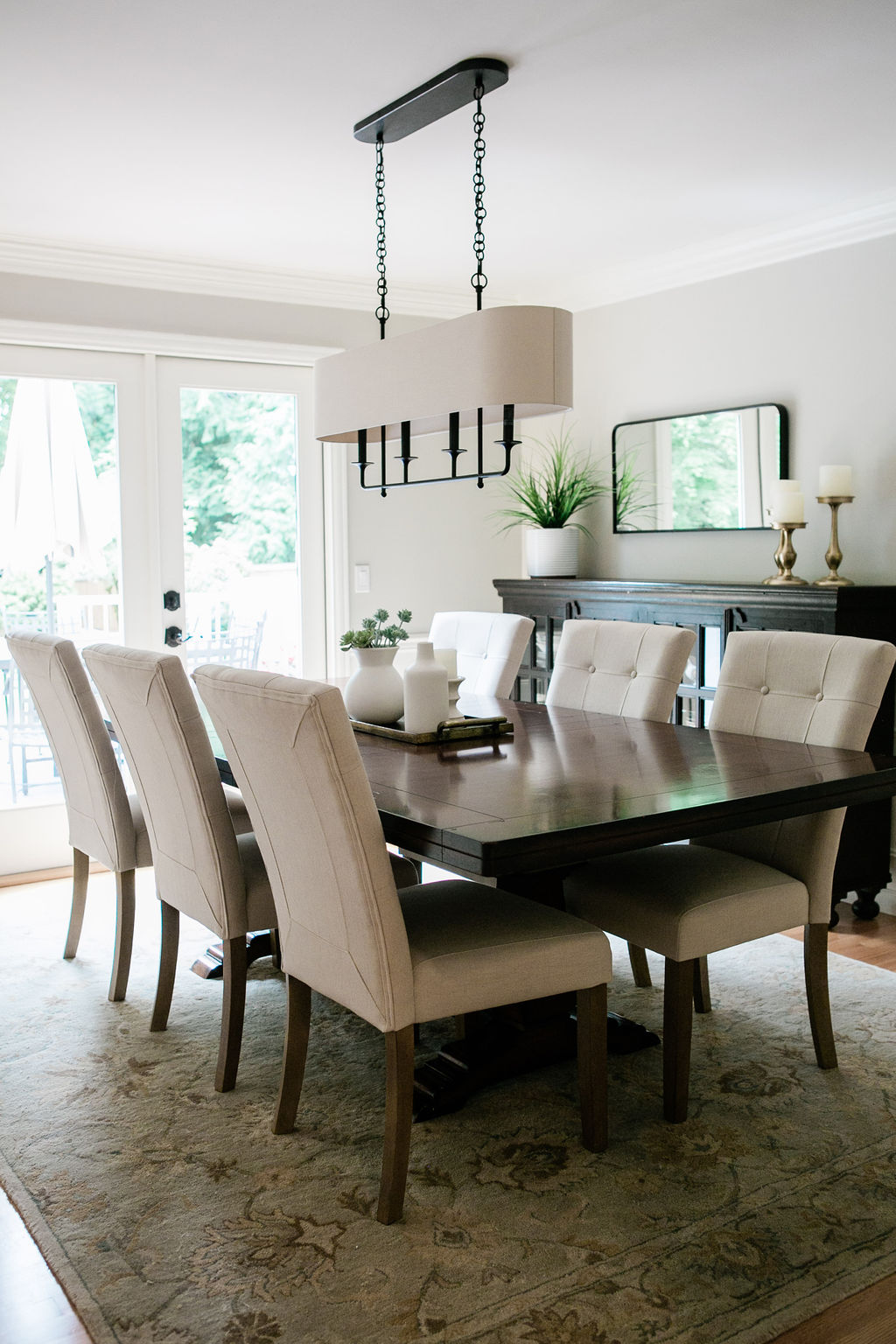Button tufted parson style dining room chairs and a chandelier with a linen shade.
