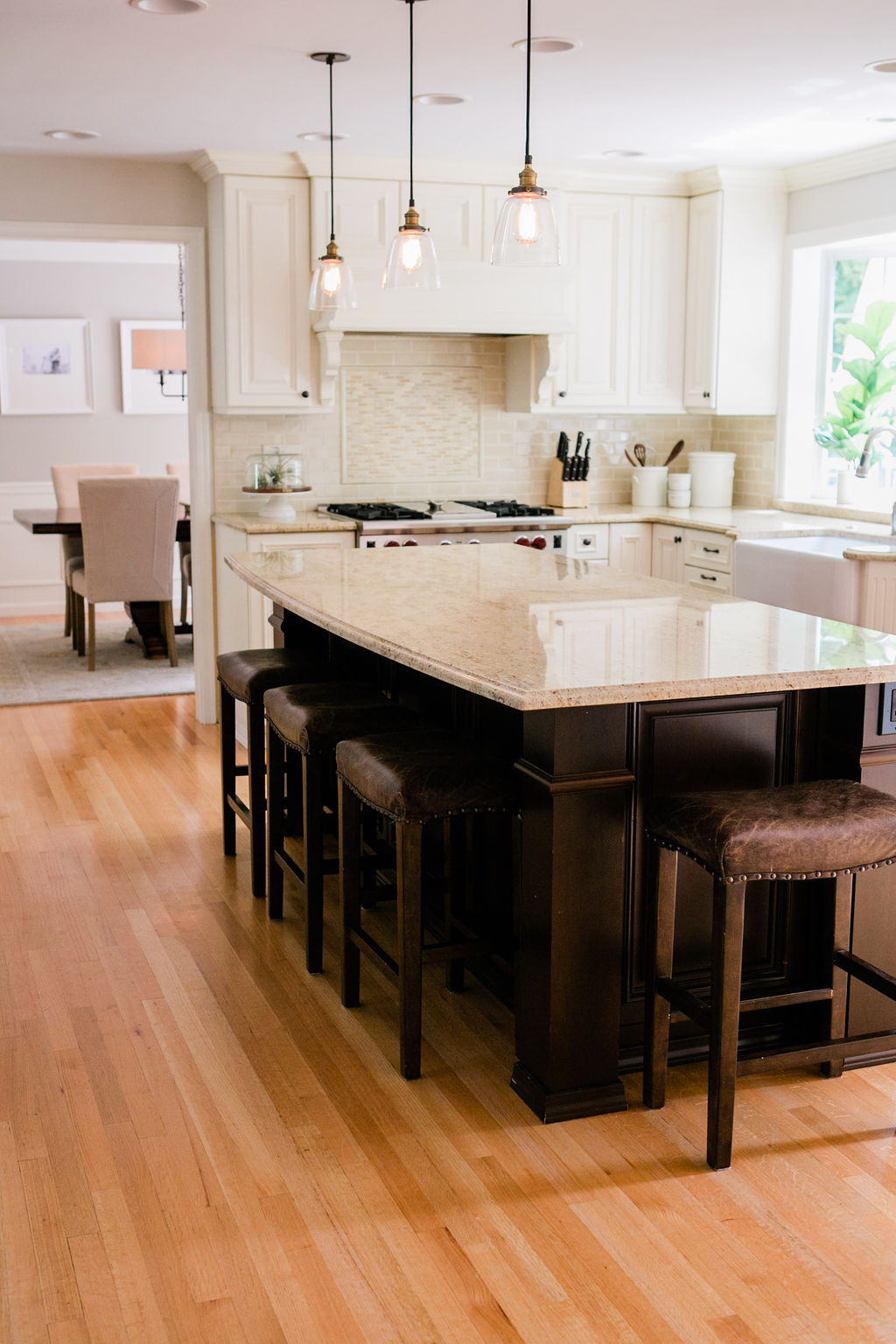 Large kitchen island with granite countertops and restoration hardware pendants.