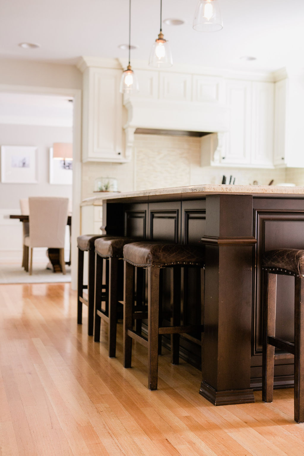 Stunning hardwood floors with leather barstools in a traditional kitchen with wolf appliances.