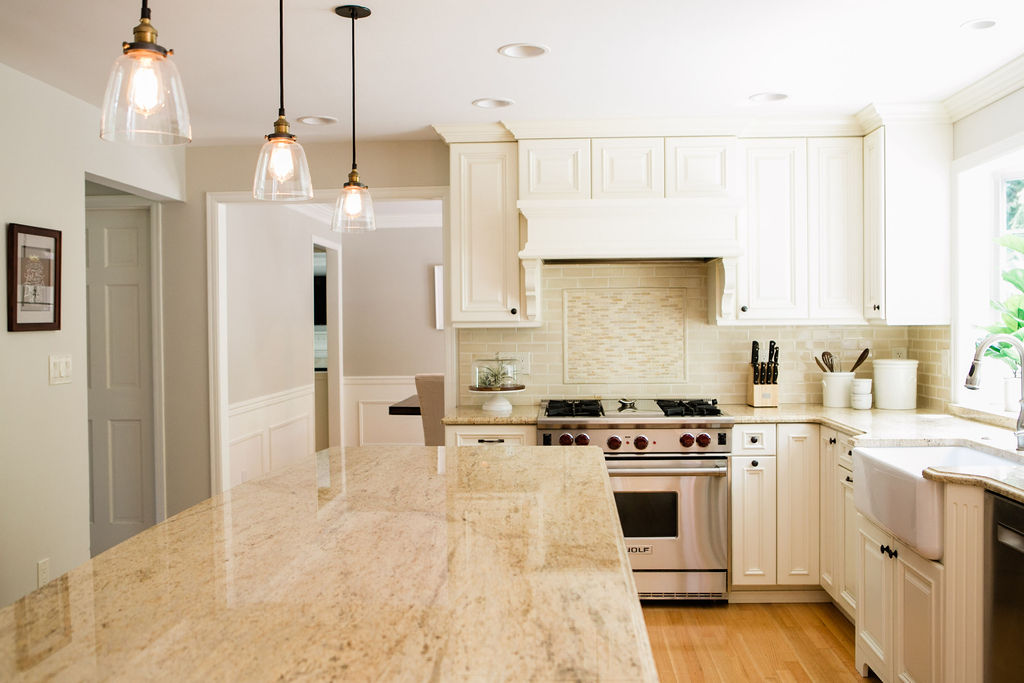 Wolf range, granite countertops, restoration hardware pendants in a traditional kitchen with white cabinetry.