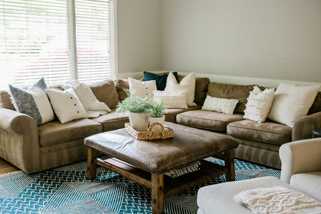 Traditional sectional sofa and leather ottoman with pillows.