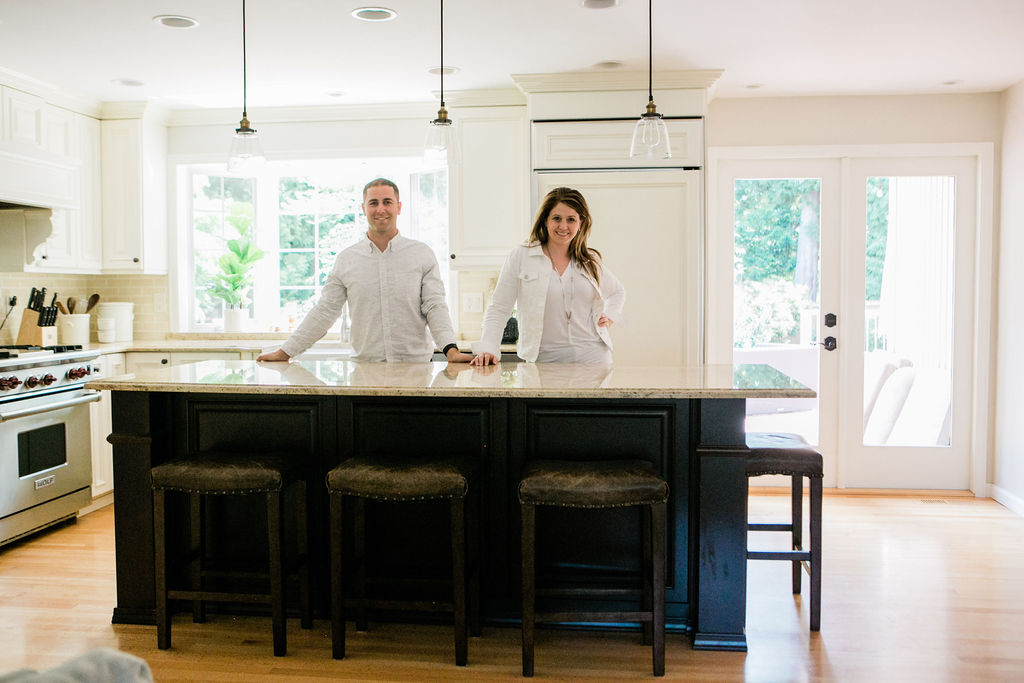 Interior Designers and decorators John and Sherri Monte behind the island of a clients kitchen.