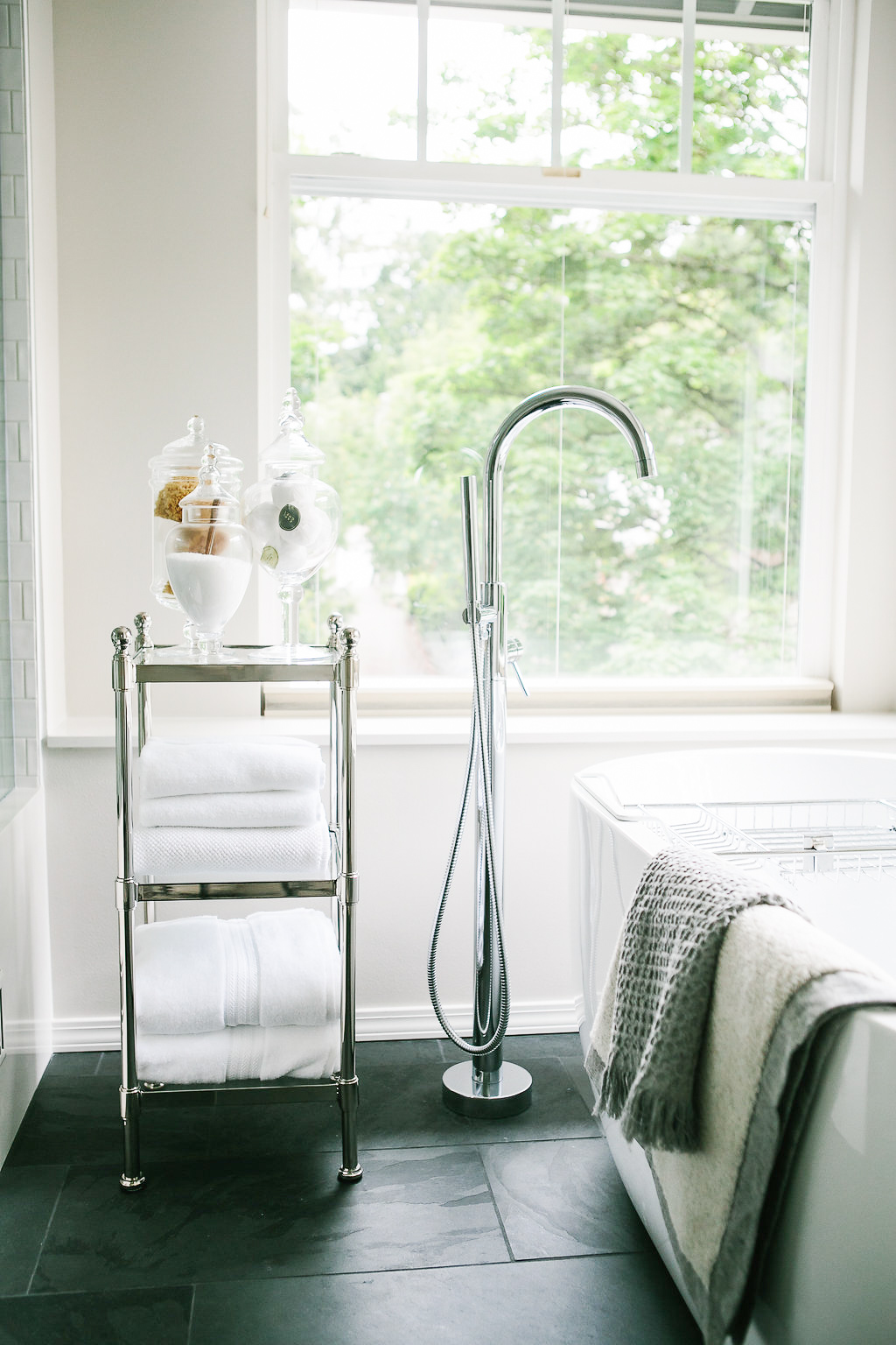 Polished nickel bath cart with white towels and a free standing tub faucet.