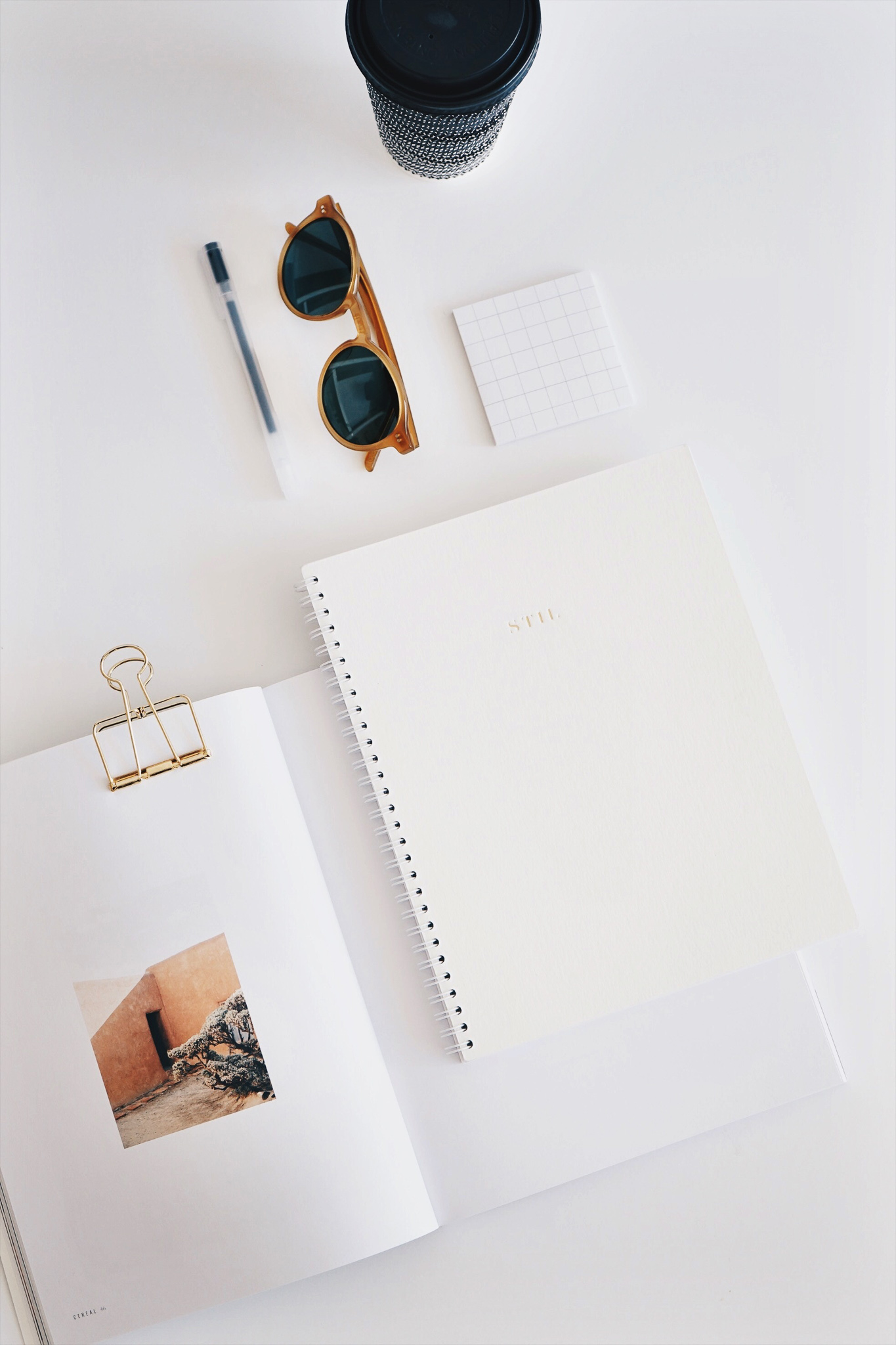 A paper day planner, a journal and sunglasses.