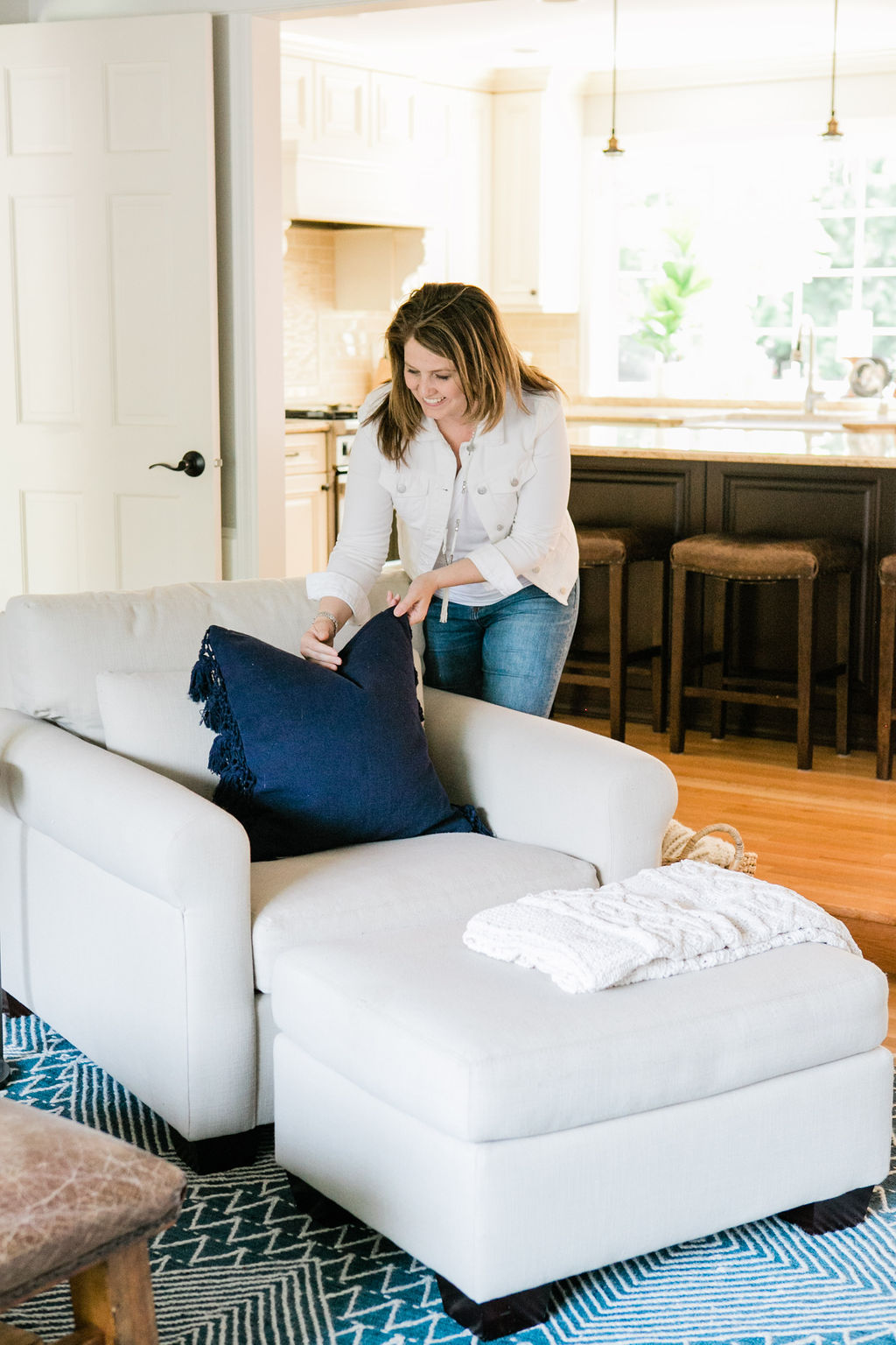A pottery barn arm chair with a navy throw and interior designer, Sherri Monte.