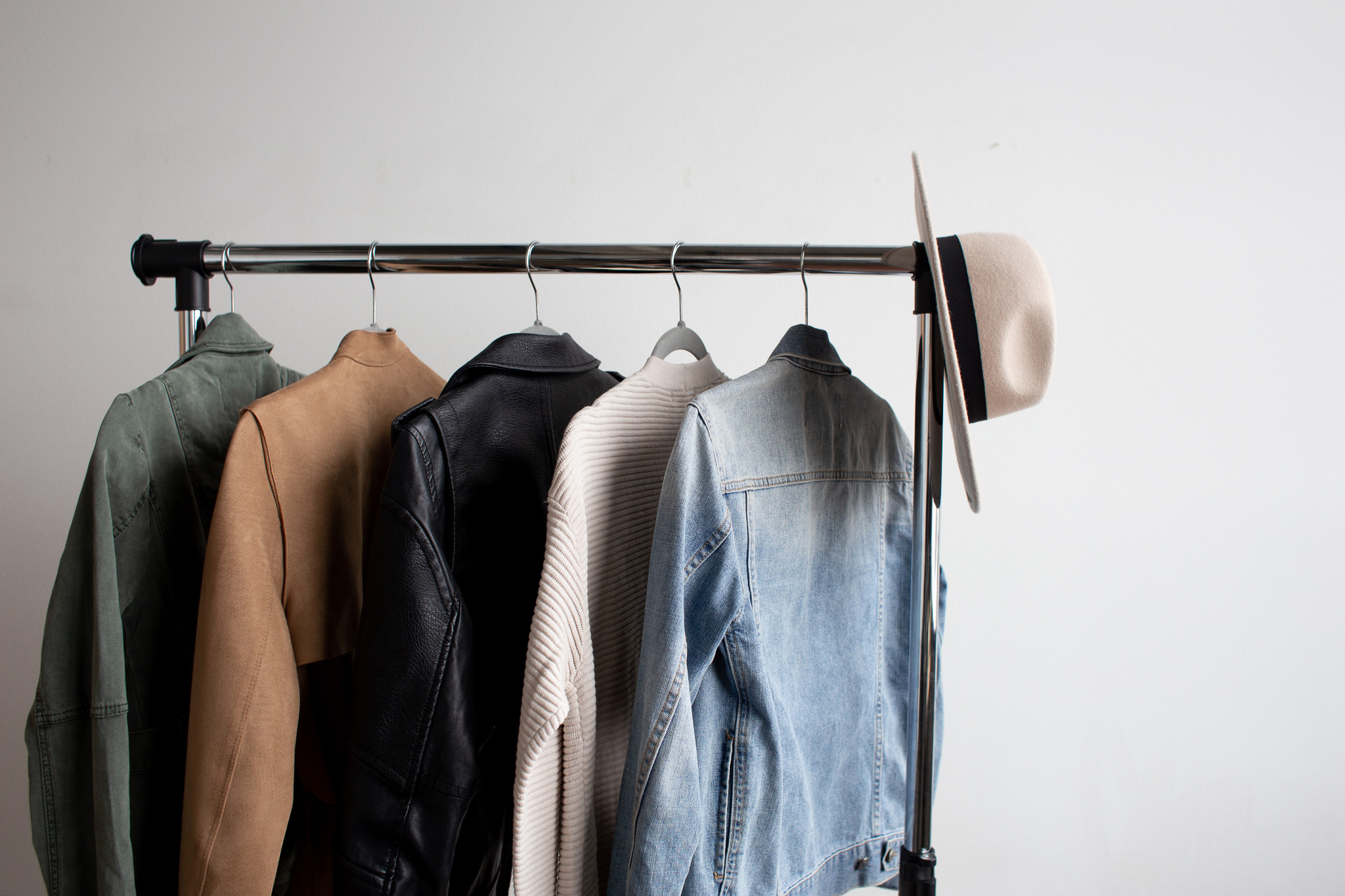 Sweaters, leather jackets and a hat hanging on a modern clothes rod.