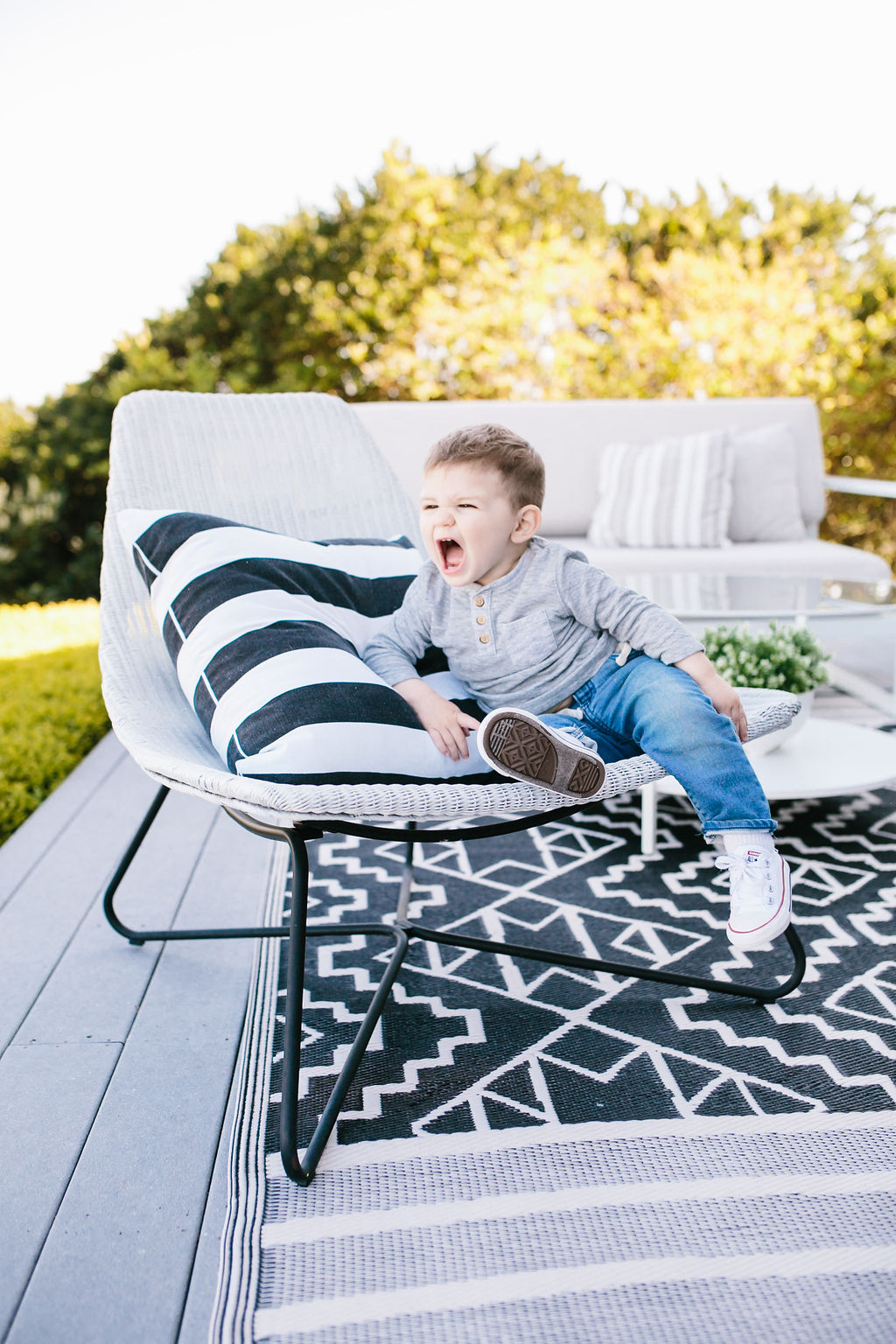 Toddler seated on a chair in an outdoor living space.