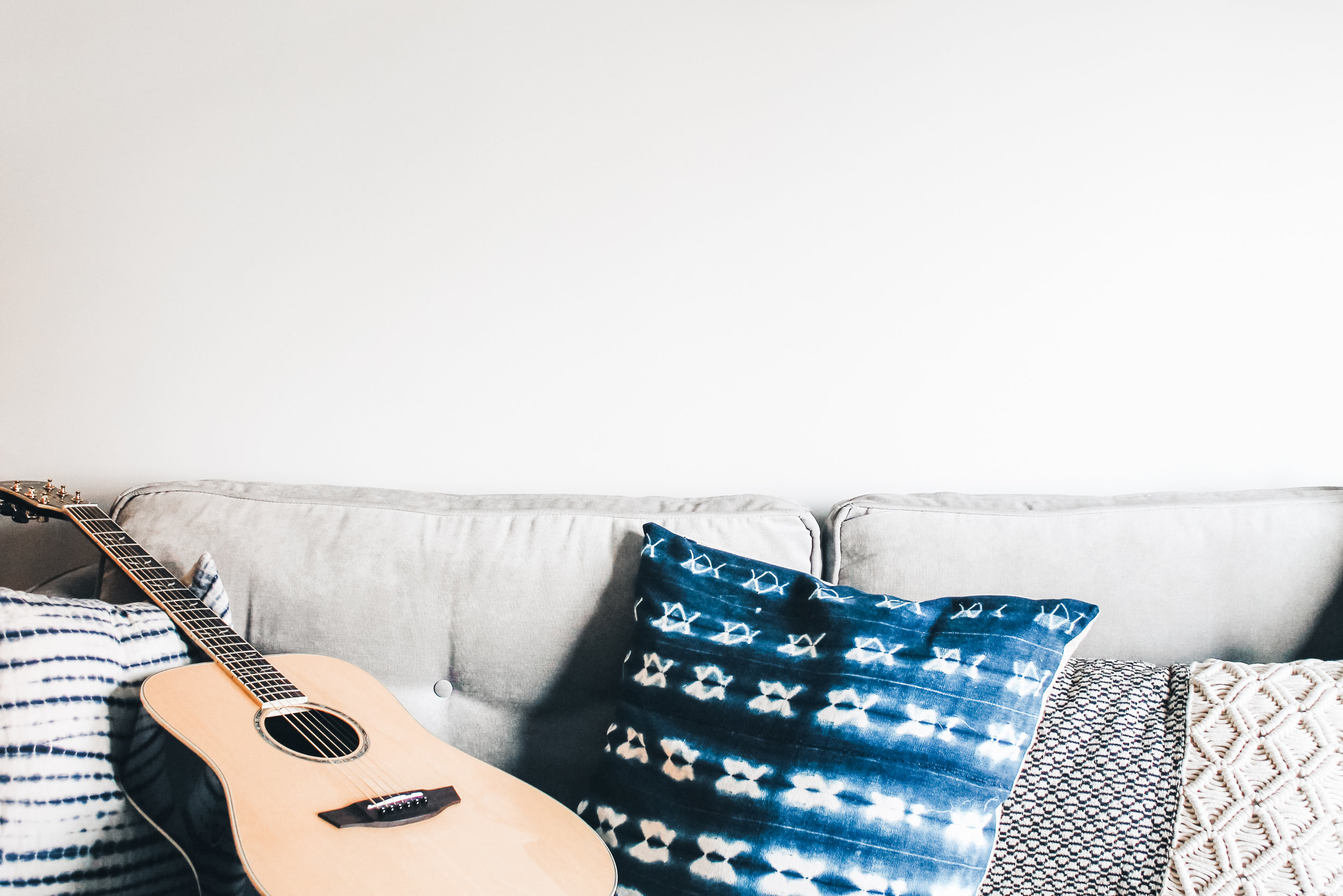 A guitar on a gray sofa with accent throw pillows in geometric patters and navy blue.