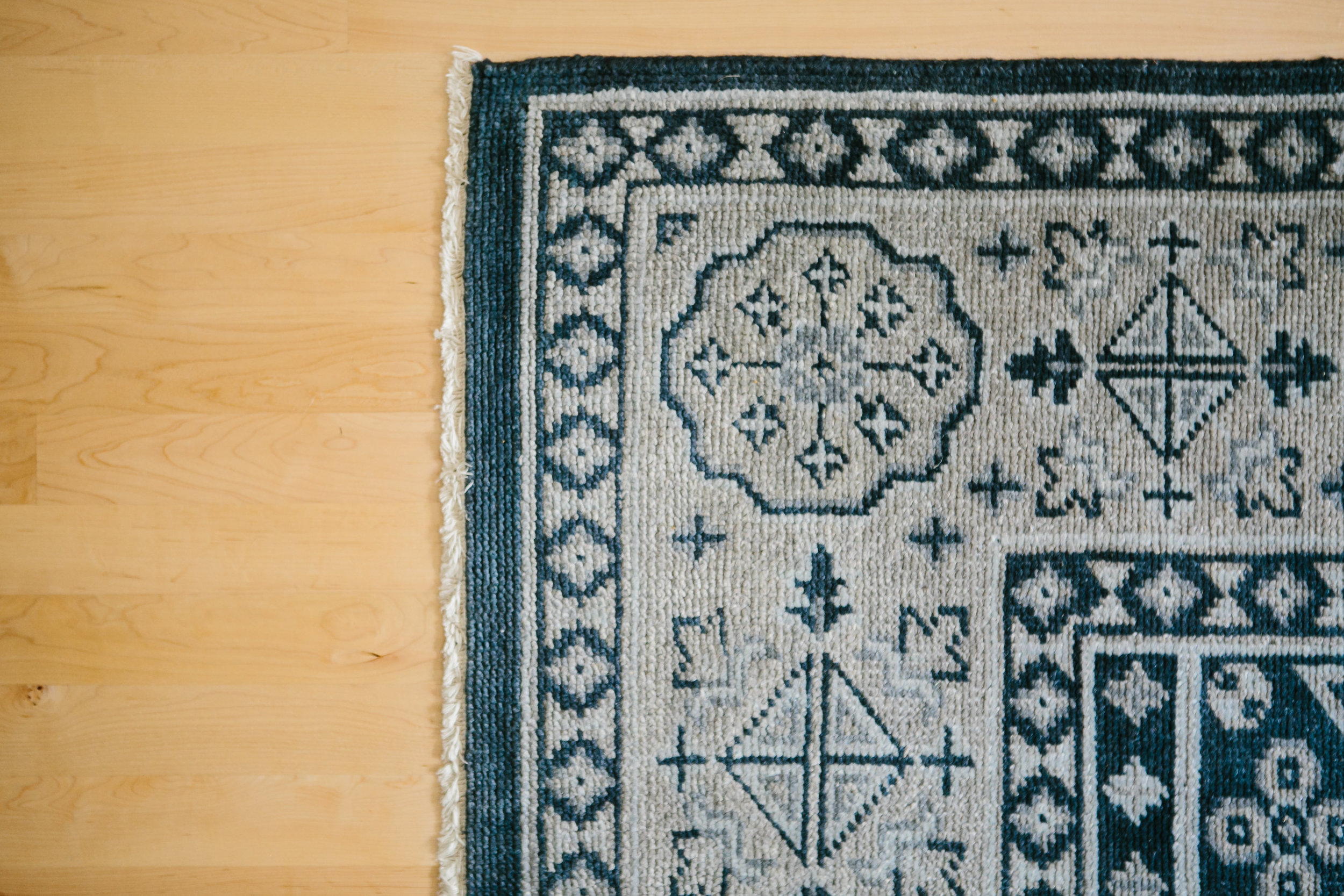A heavily patterned Moroccan rug in navy blue and gray on light blonde hardwood floors.