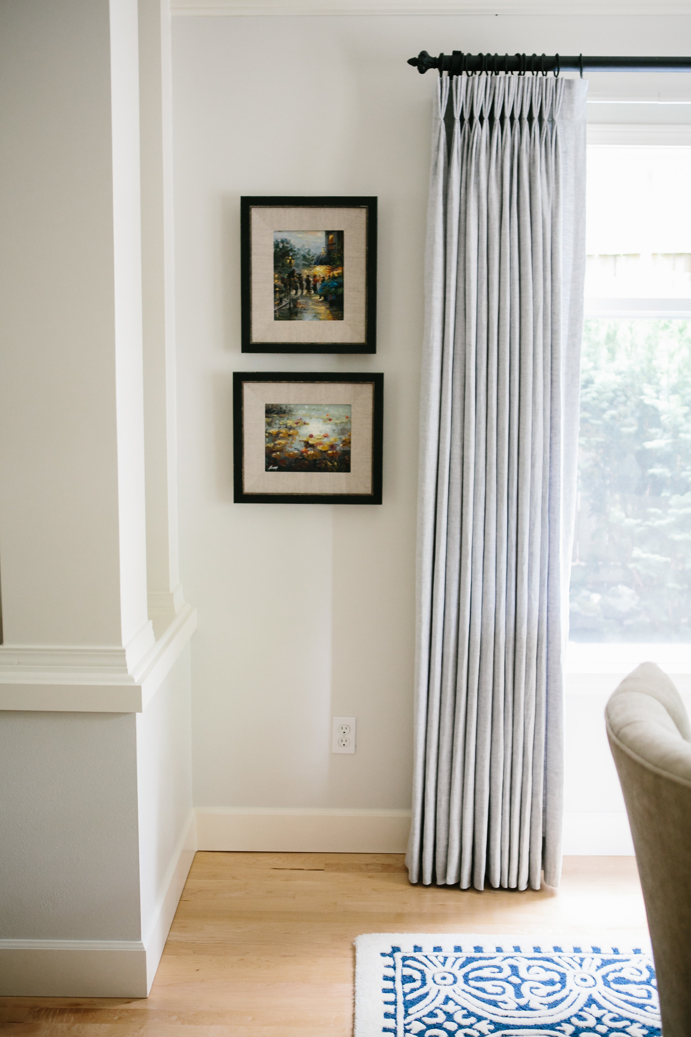 Ripple fold drapery in a Kirkland, Washington home with blonde hardwood floors and a navy blue rug.