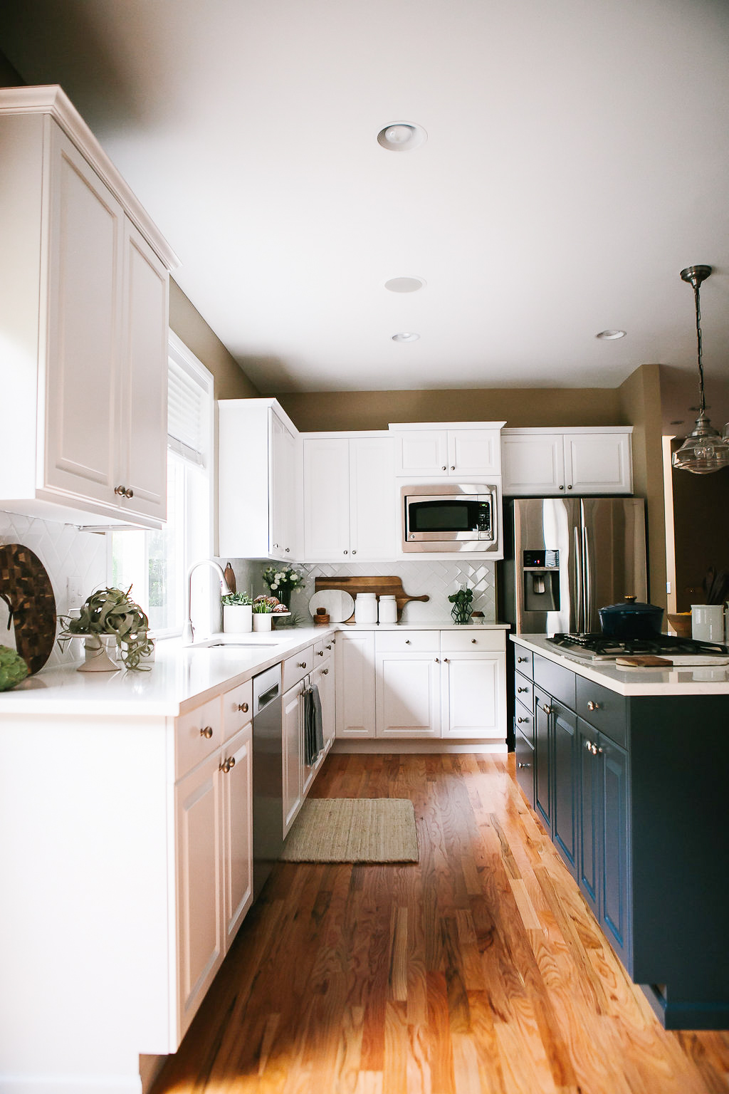 A transitional white kitchen with navy blue island designed by Elegant Simplicity.