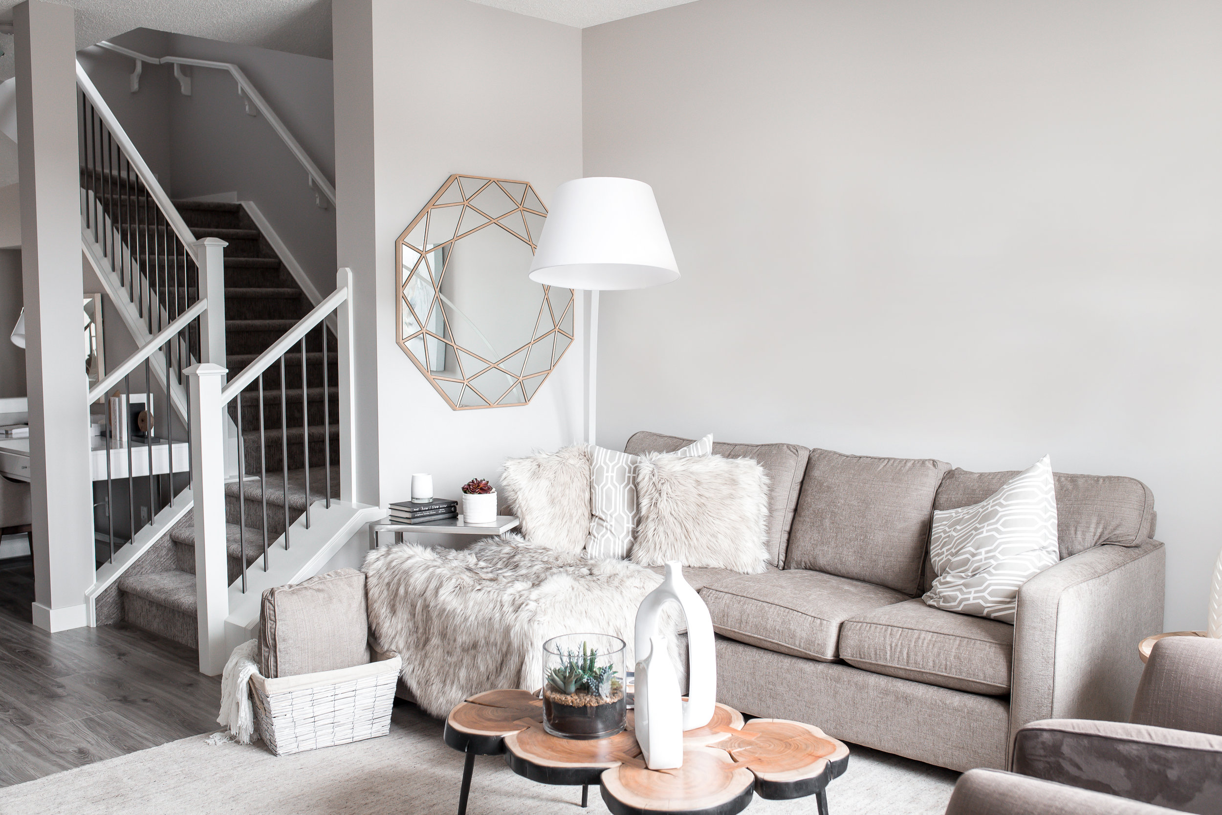 Soft grey walls with white trim in a neutral living room with natural wood accent tables.