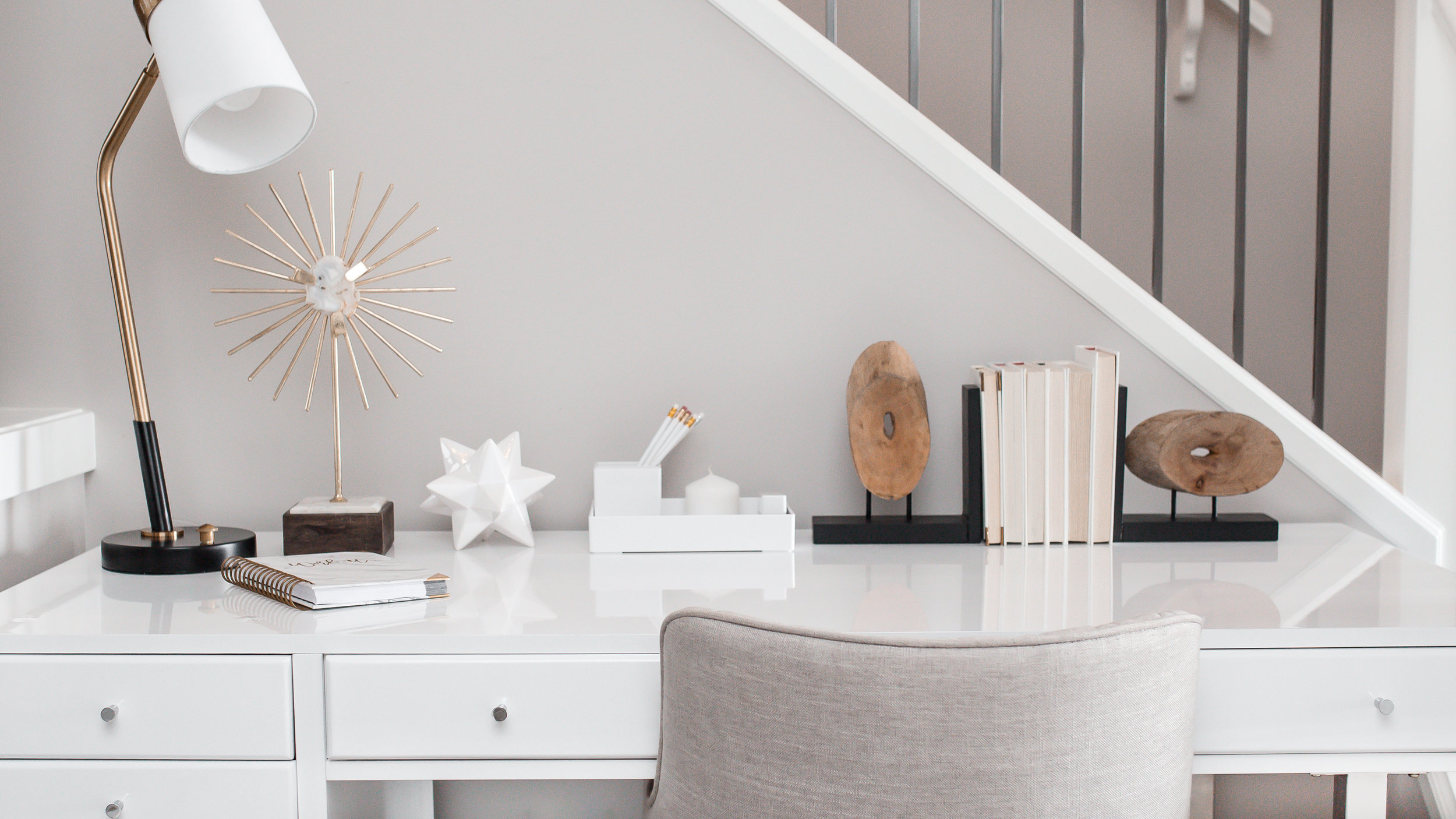 A white desk with office decor and an upholstered chair.
