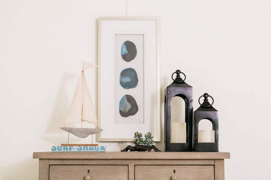 Decorative accents, books and lanterns sit atop a weather gray dresser in the master bedroom of this Warm Beach cabin.