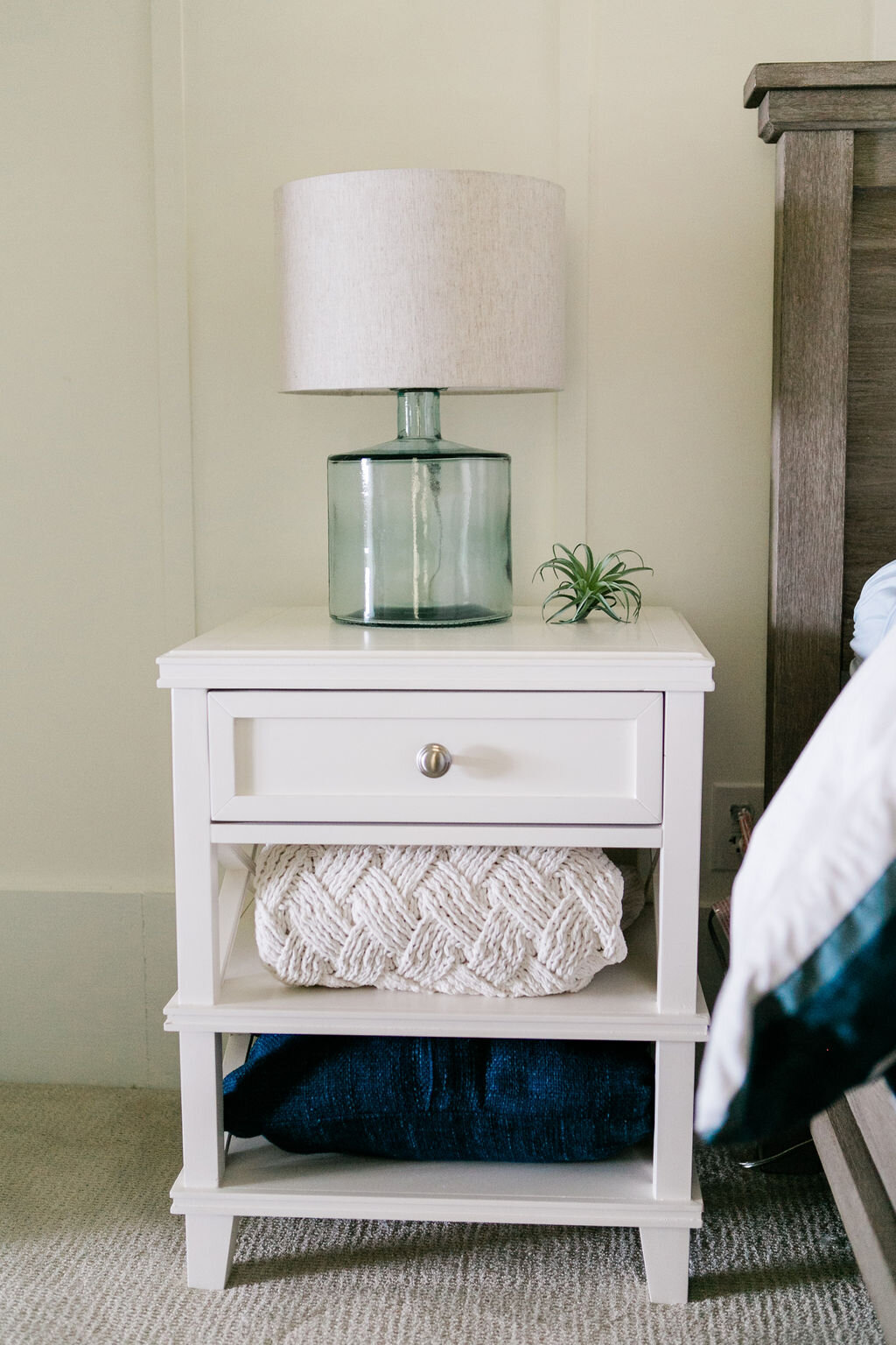 White wood nightstands with decorative throw blankets and a soft blue glass side table lamp.