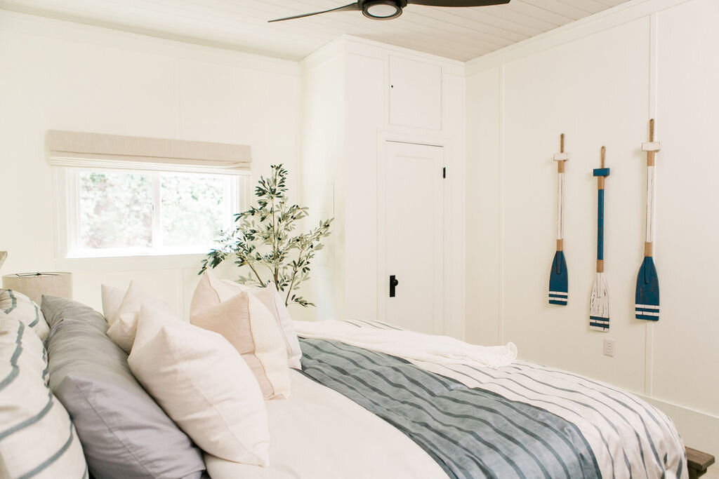 A coastal modern master bedroom with light blue hues and weather oars hung on the wall.