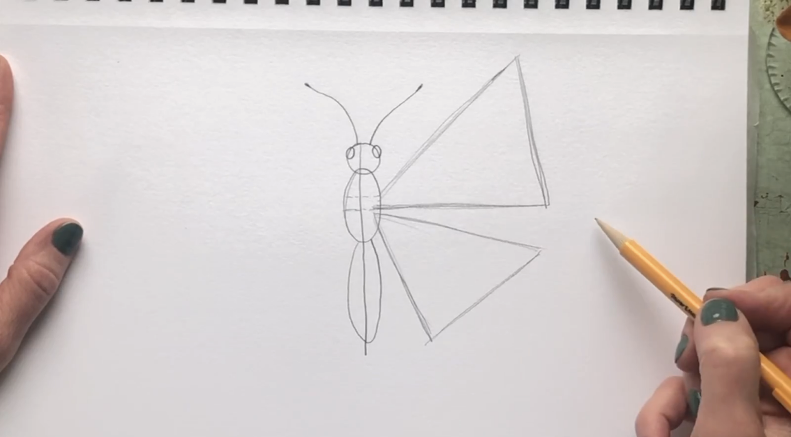 Place the bottom wing by drawing a slightly tilted triangle coming out from the same area.