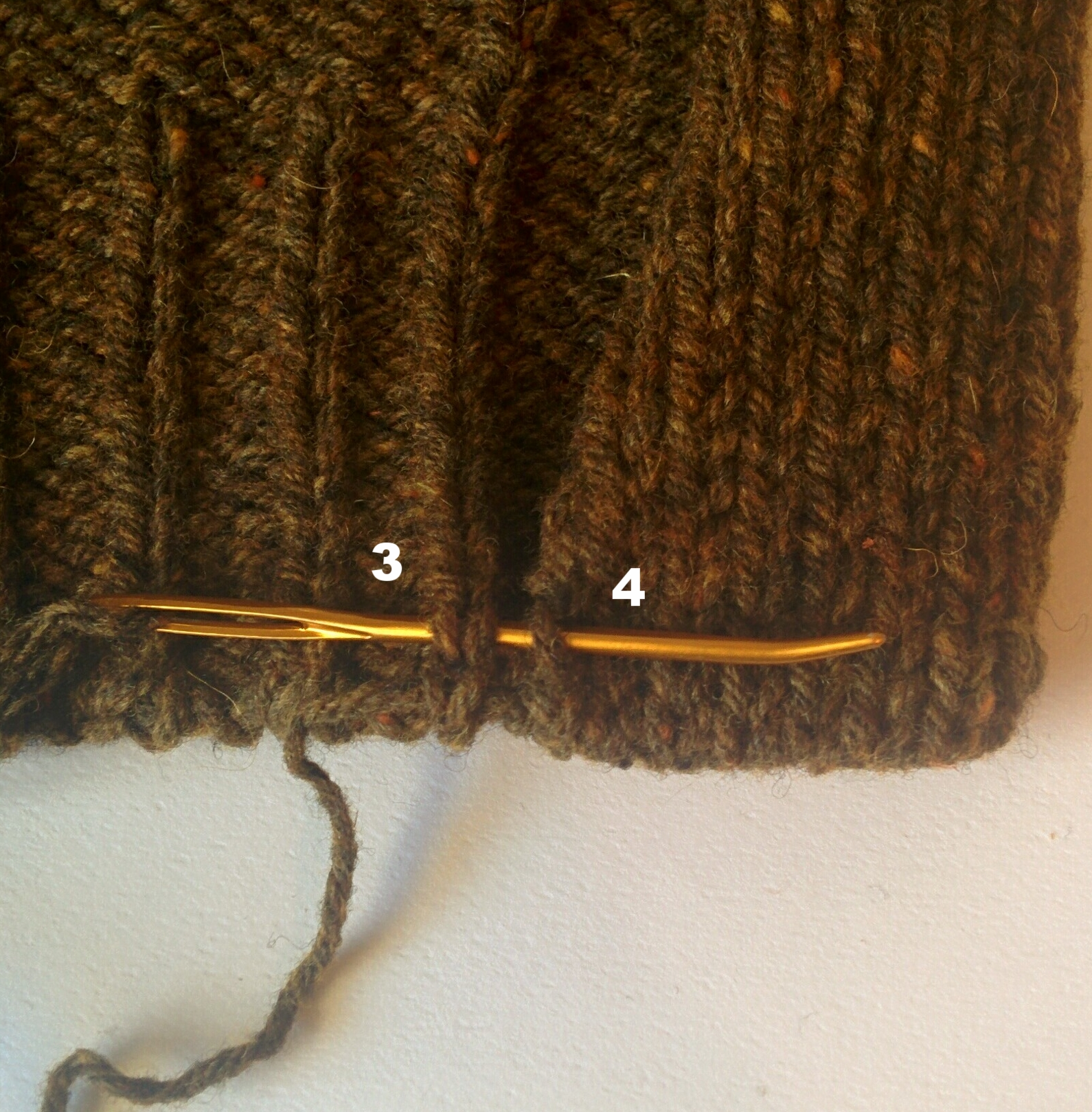 3) Insert needle from left to right under both legs of reverse St st above.  4) Insert needle from WS to RS through center of outermost st of facing in row above and pull yarn through.