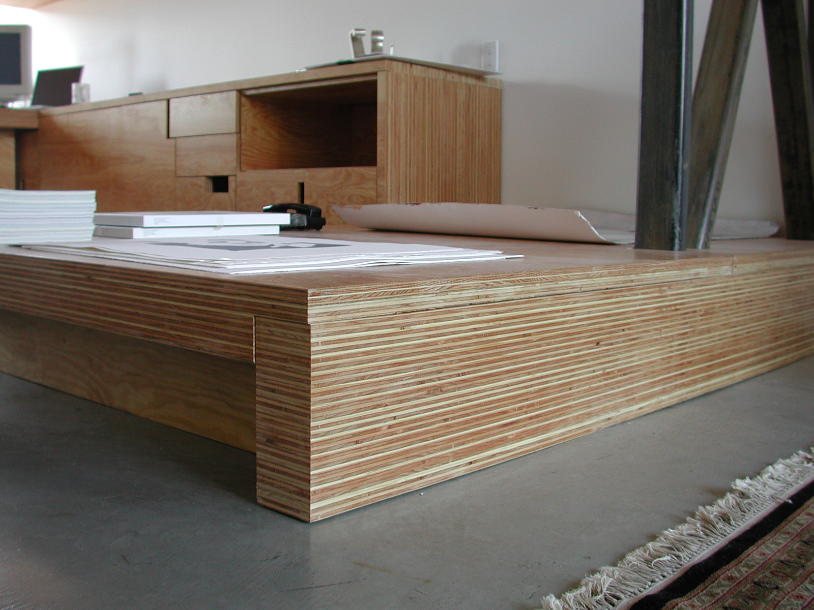 Detail of how the daybed relates to the floor as a continuation of the countertop surface of the cabinetry.