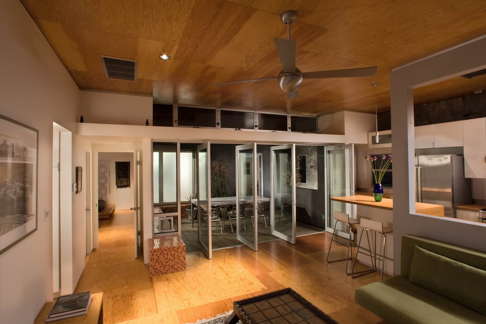 The living room doors can be configured to maximize the indoor-outdoor experience with the dining room, as seen here at dusk.