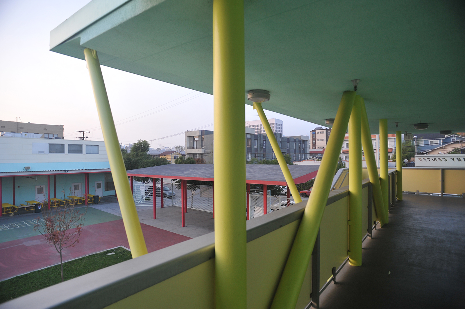 The two primary structures are connected along the northern edge by a canopy or porch-like structure. The 'public porch' canopy addresses both the school and the neighborhood.