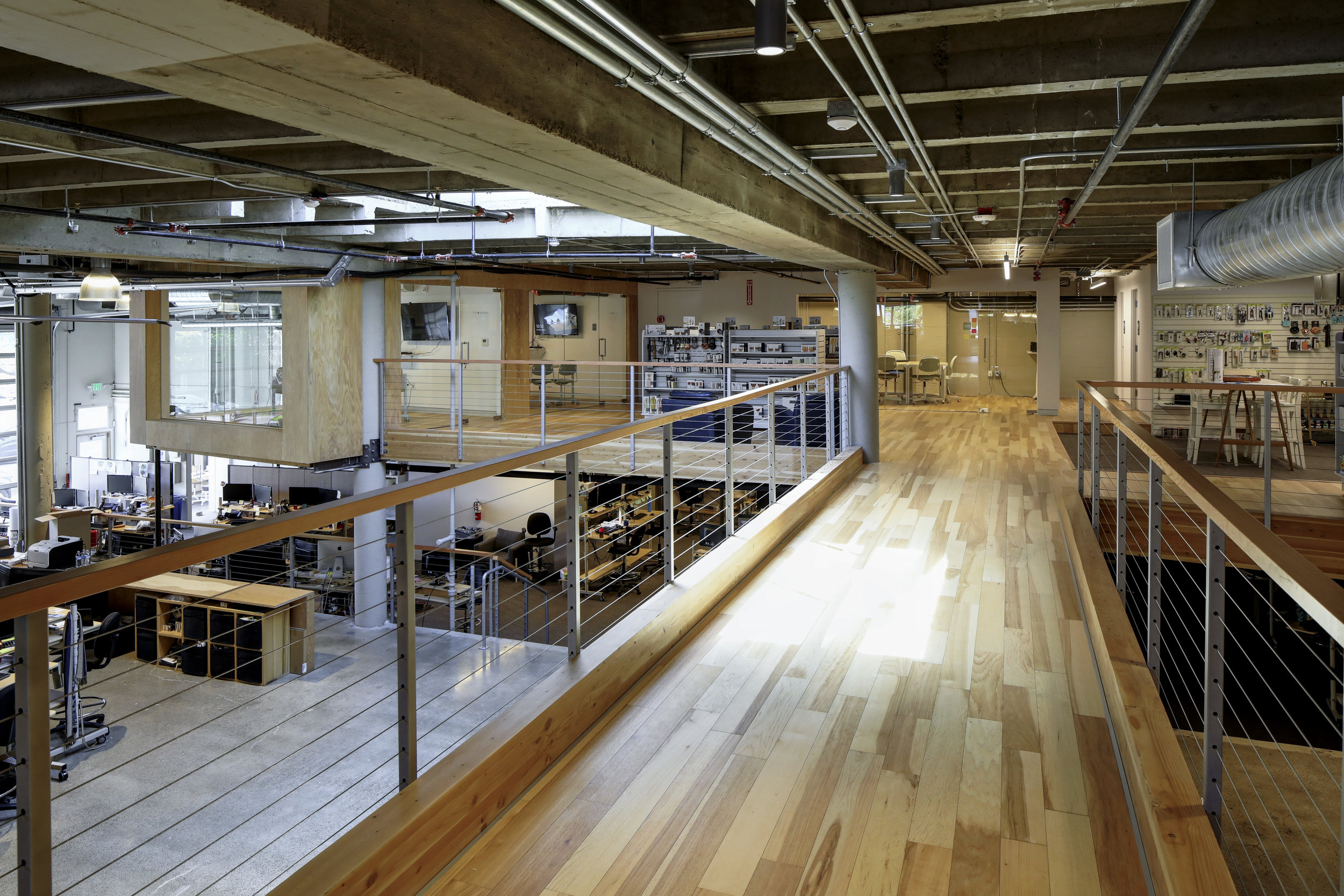 The space is entered at the foot of a bridge spanning two mezzanines and overlooking the main work floor.