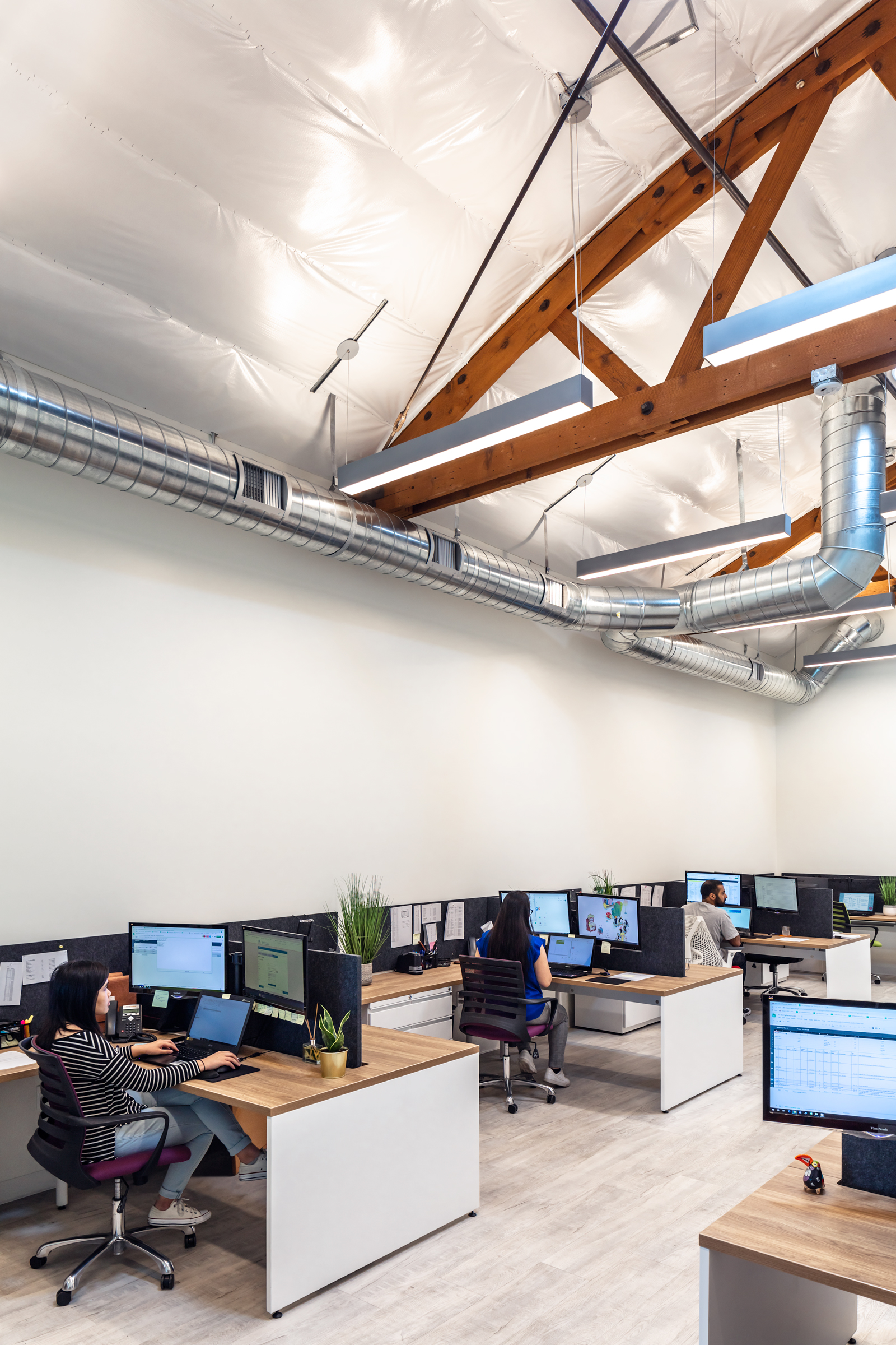 The open plan workstations benefiting from the dramatic space above