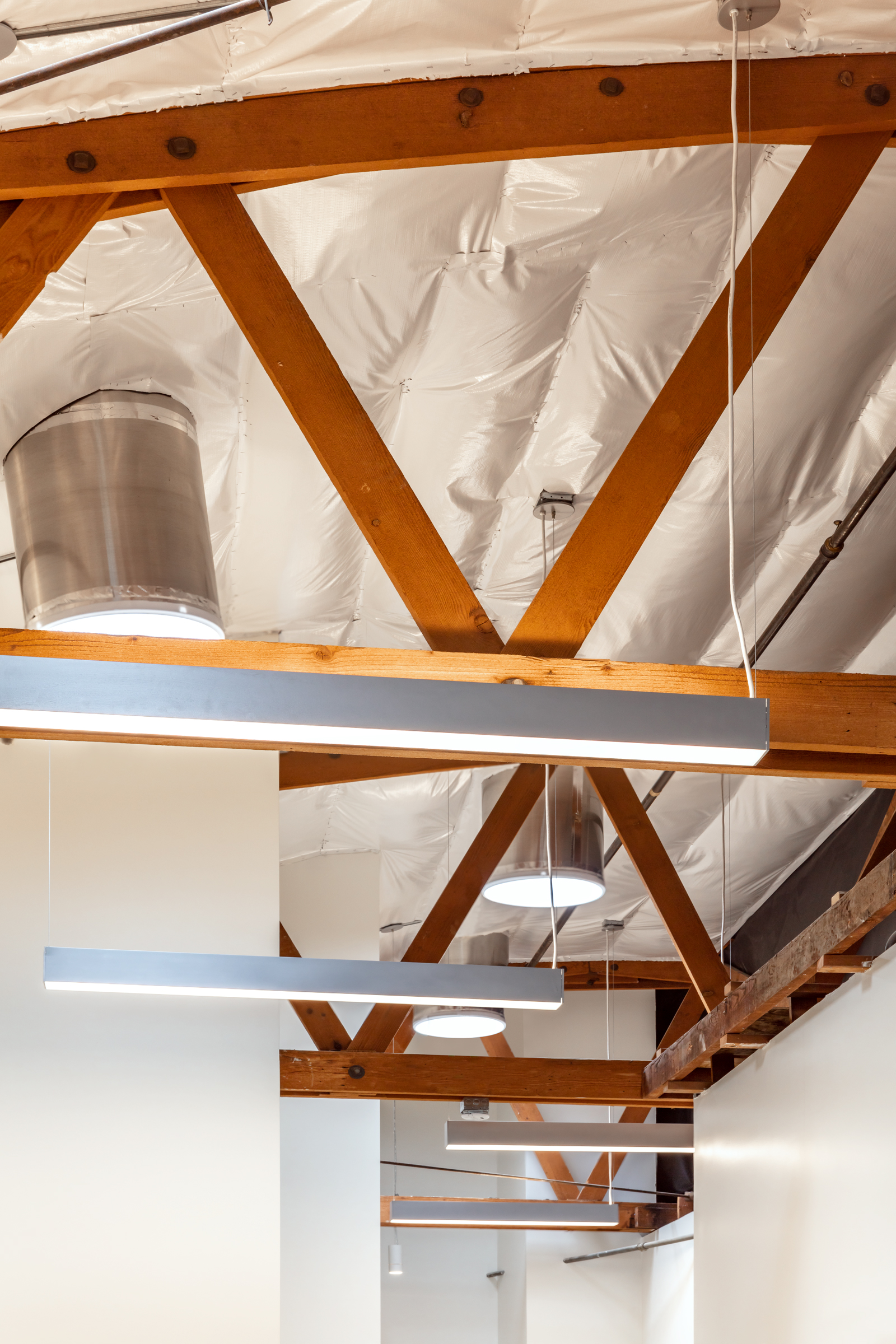 The removal of the dropped ceiling creates a dramatic verticality to the space, exposes the warmth of the existing wood bow trusses, and creates the opportunity to admit daylight via solatubes