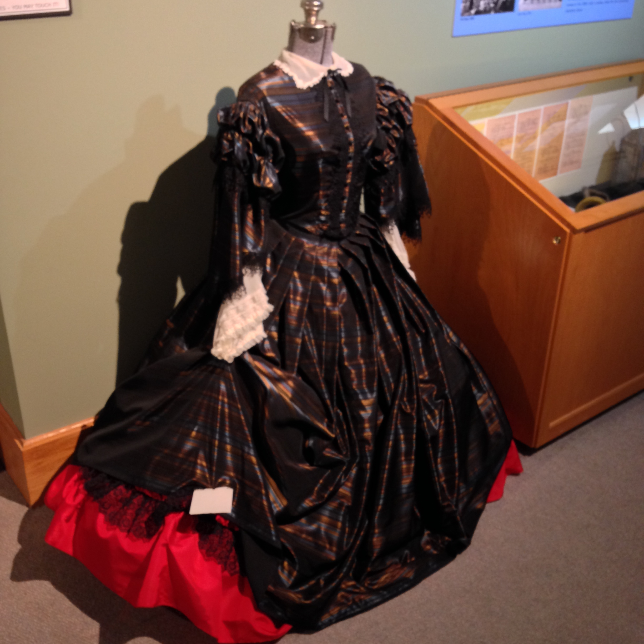 Style choices in the 1850s are illustrated by this dress reproduction: a collar, cinched waist, and multiple skirt layers were all popular.