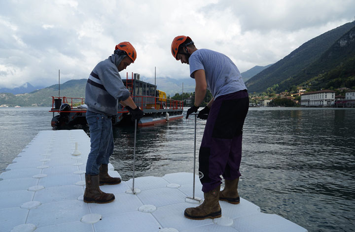 Construction workers assemble the first floating segment by connecting the polyethylene cubes