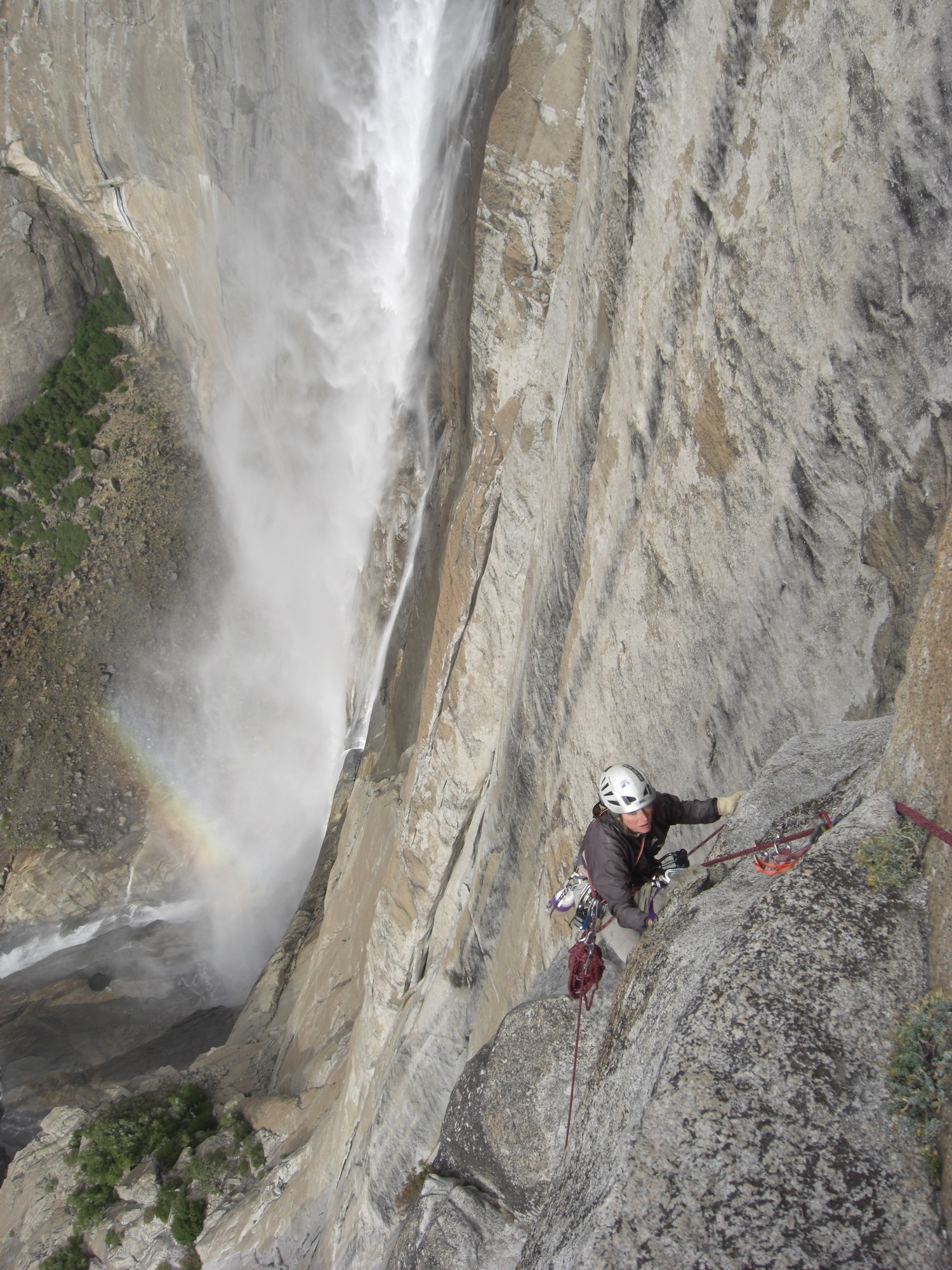 Lisa Van Sciver climbs Lost Arrow Spire Direct, Yosemite Falls in the background. Yosemite National Park, California. (Photo by Emily Stifler Wolfe)