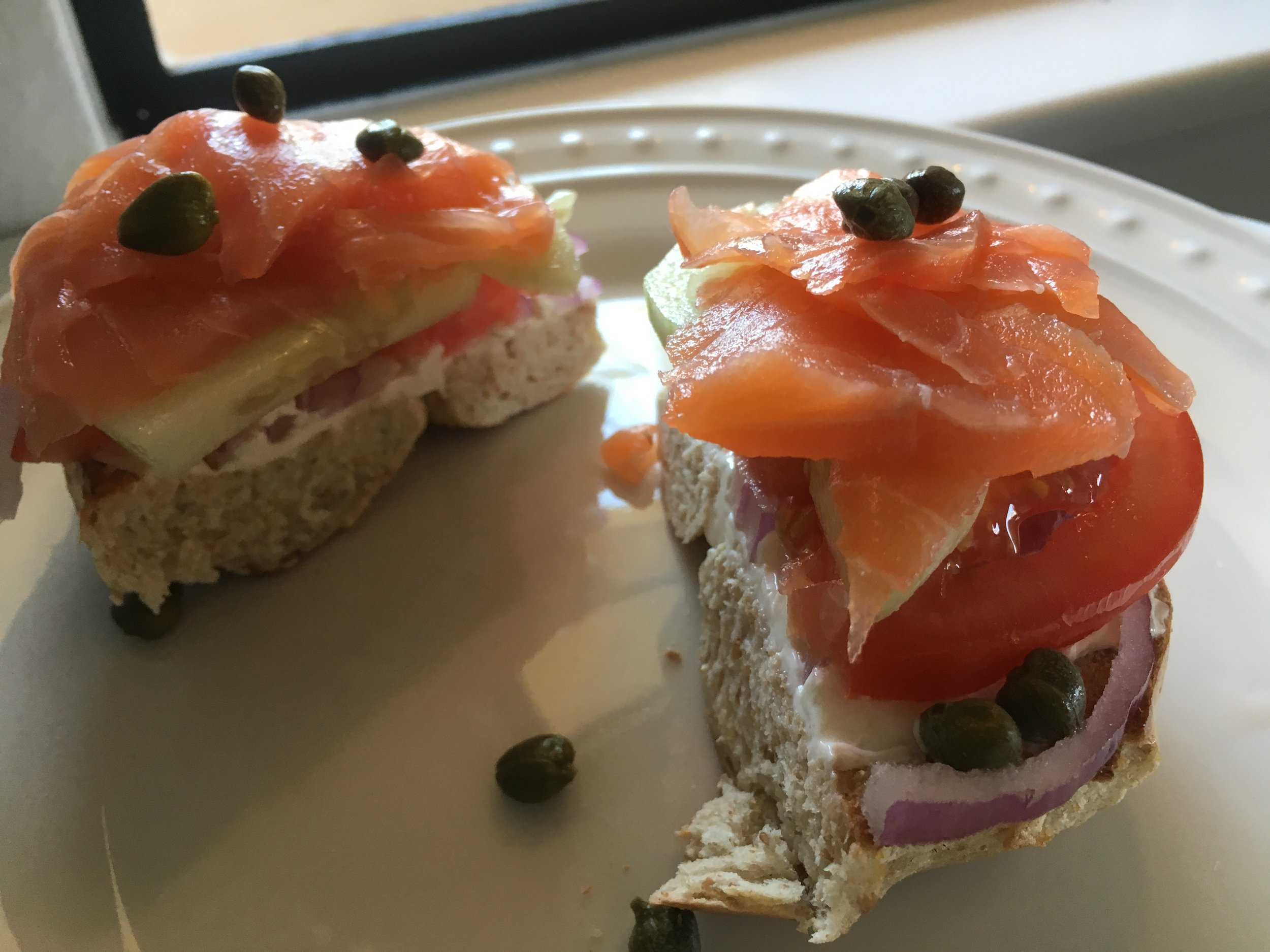Homemade bagel and lox with capers, red onions, tomato, cucumber, and cream cheese.