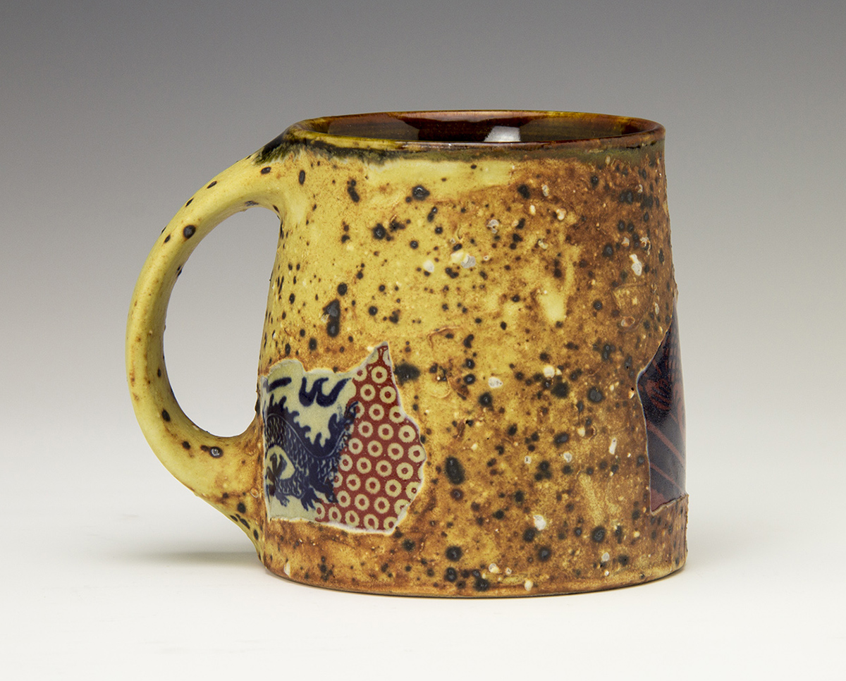 Mug with shard like decoration an textured slips made by Bruce Gholson