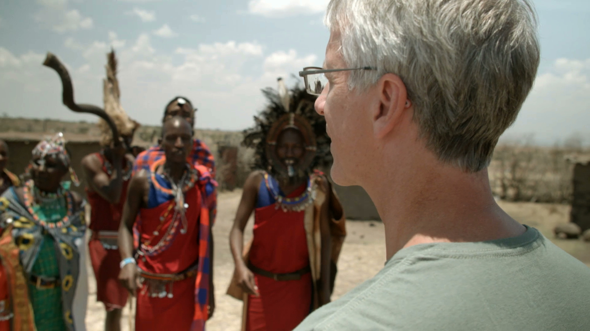 Dr. Kevin Fenton, an American choral conductor, watches a Maasai tribe perform a dance in a manyatta village in the Mara.